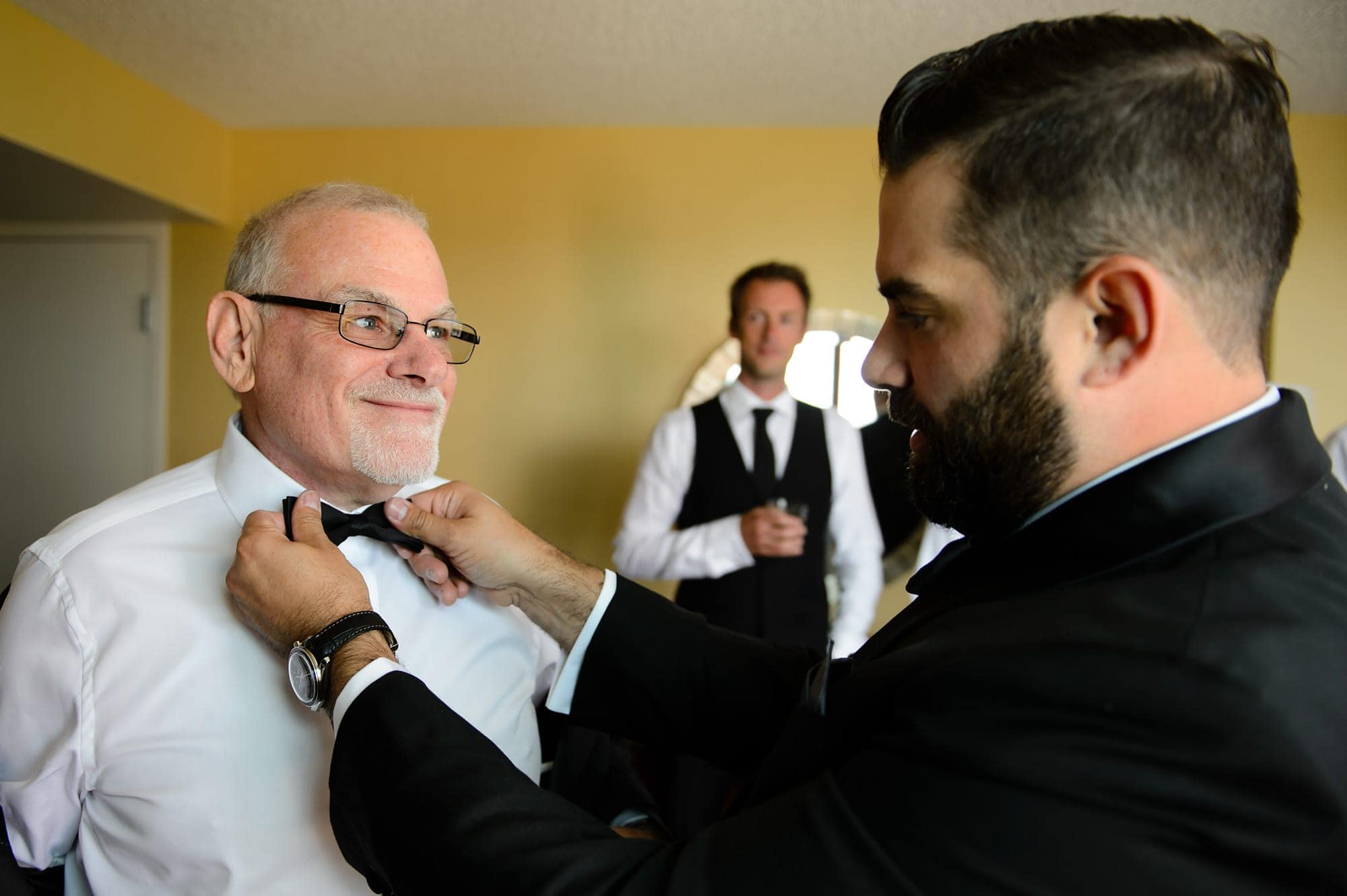 The groom adjusts his father bowtie while getting ready