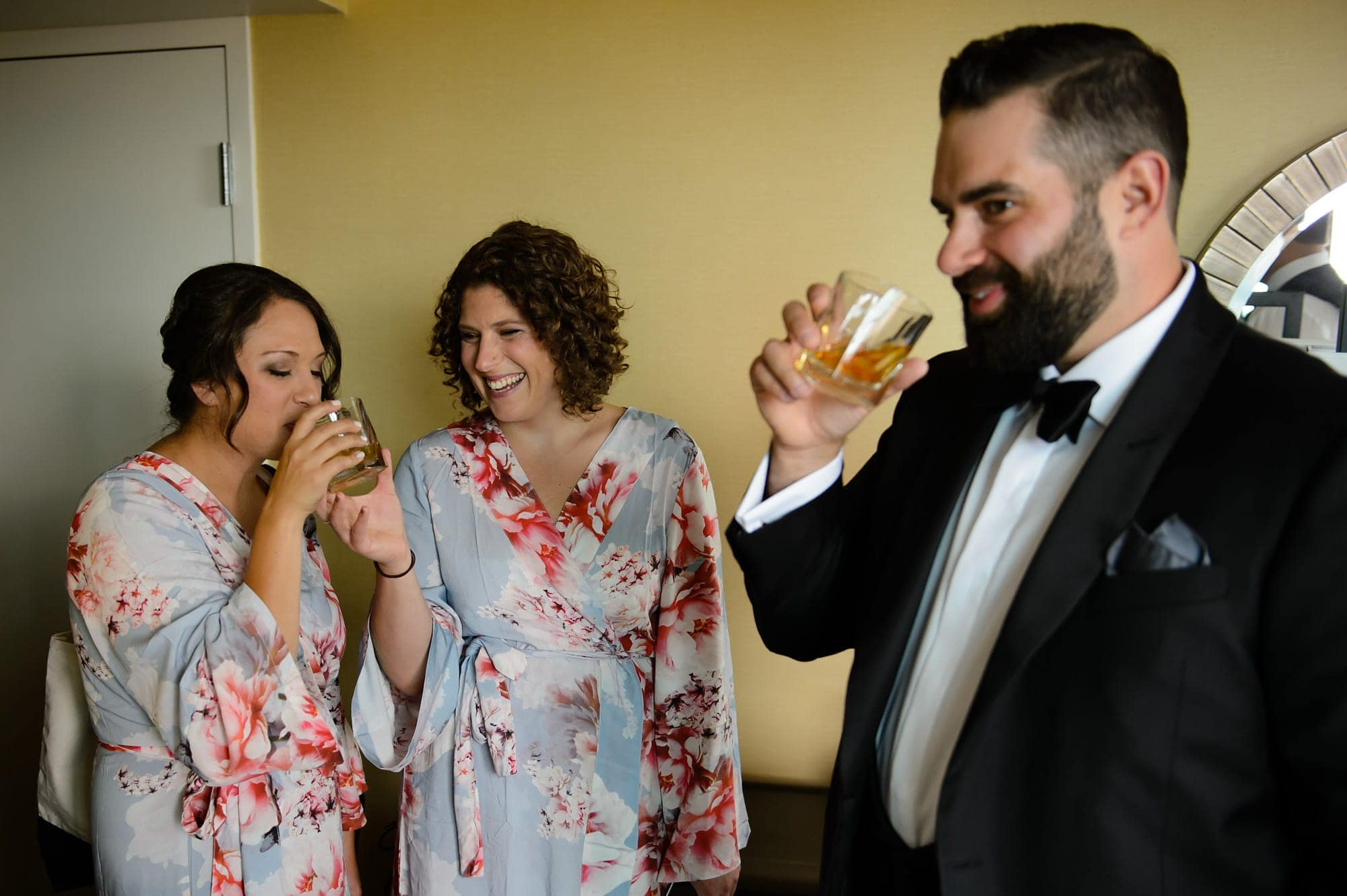 Bridesmaids in their robes share a toast of rye whiskey with the groom
