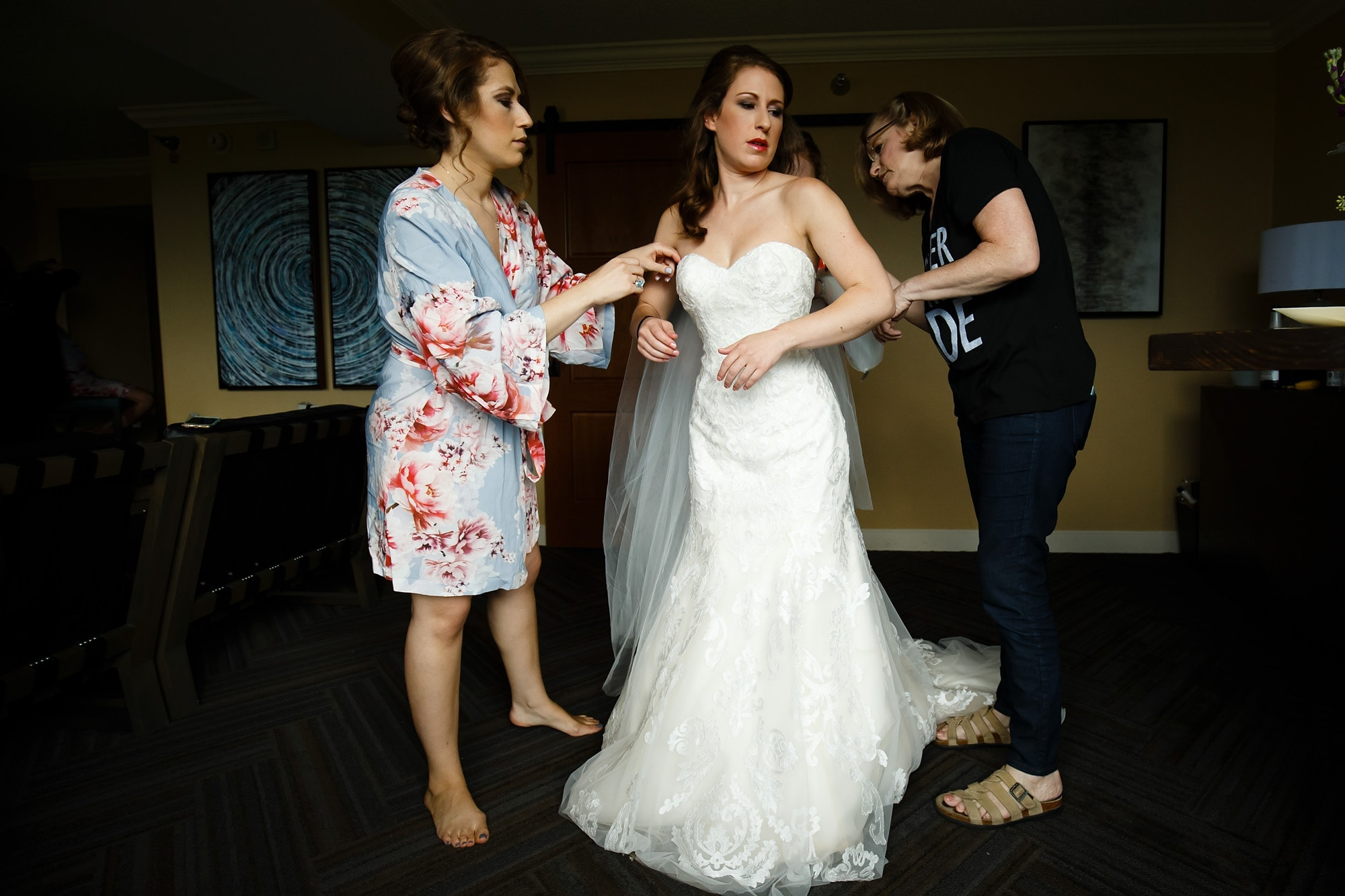 Devan gets into her wedding gown dress with the help of his sisters and mother