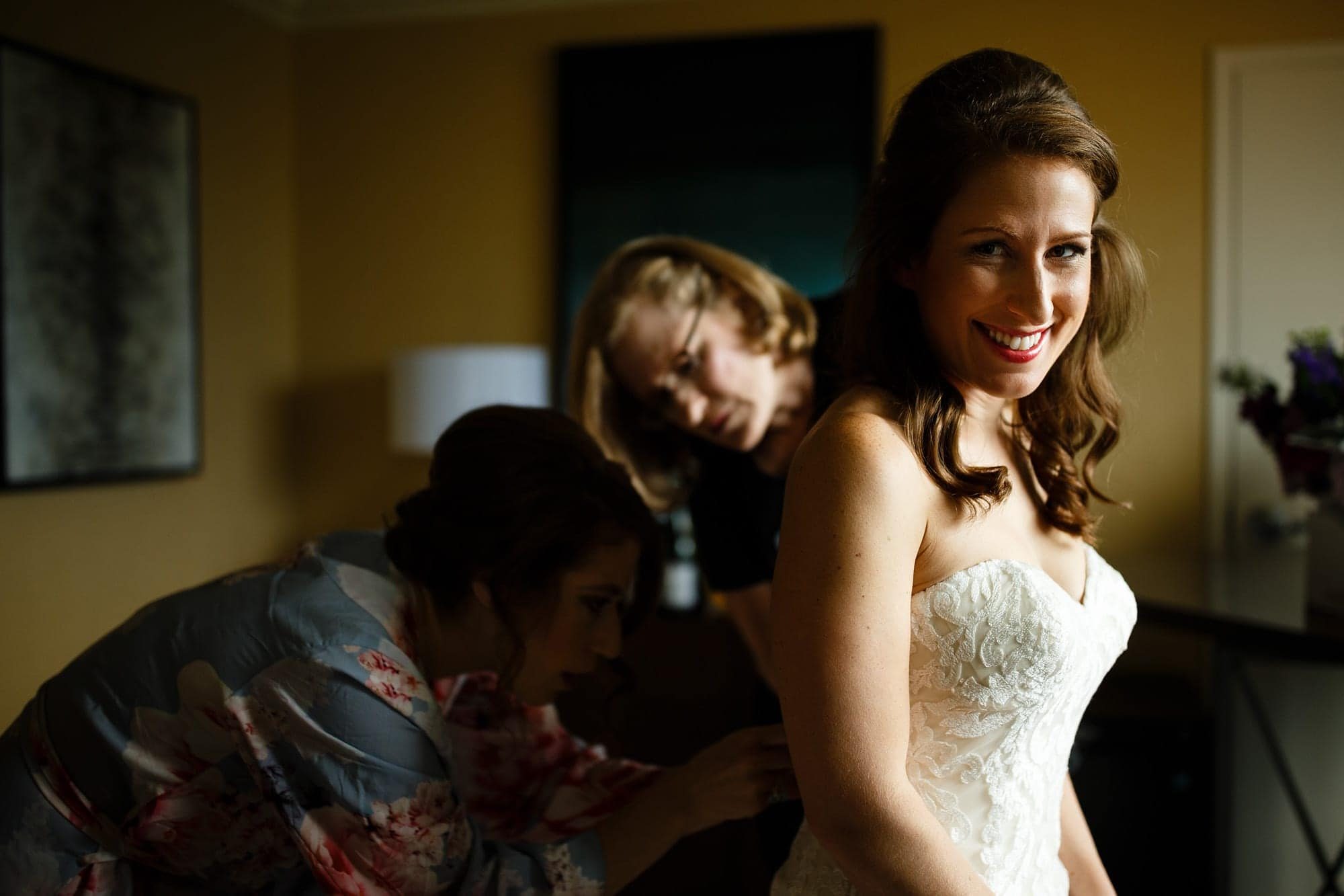 A bride has her dress adjusted by bridesmaids