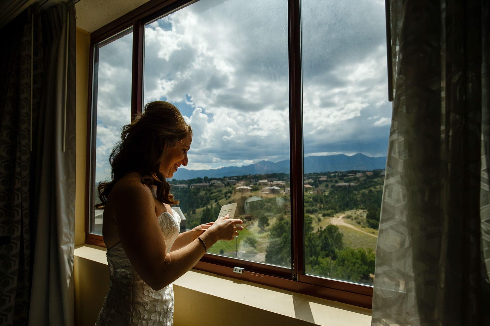 Devan reads a note from her future husband in her wedding gown while looking out towards Cheyenne Mountain and Pikes Peak