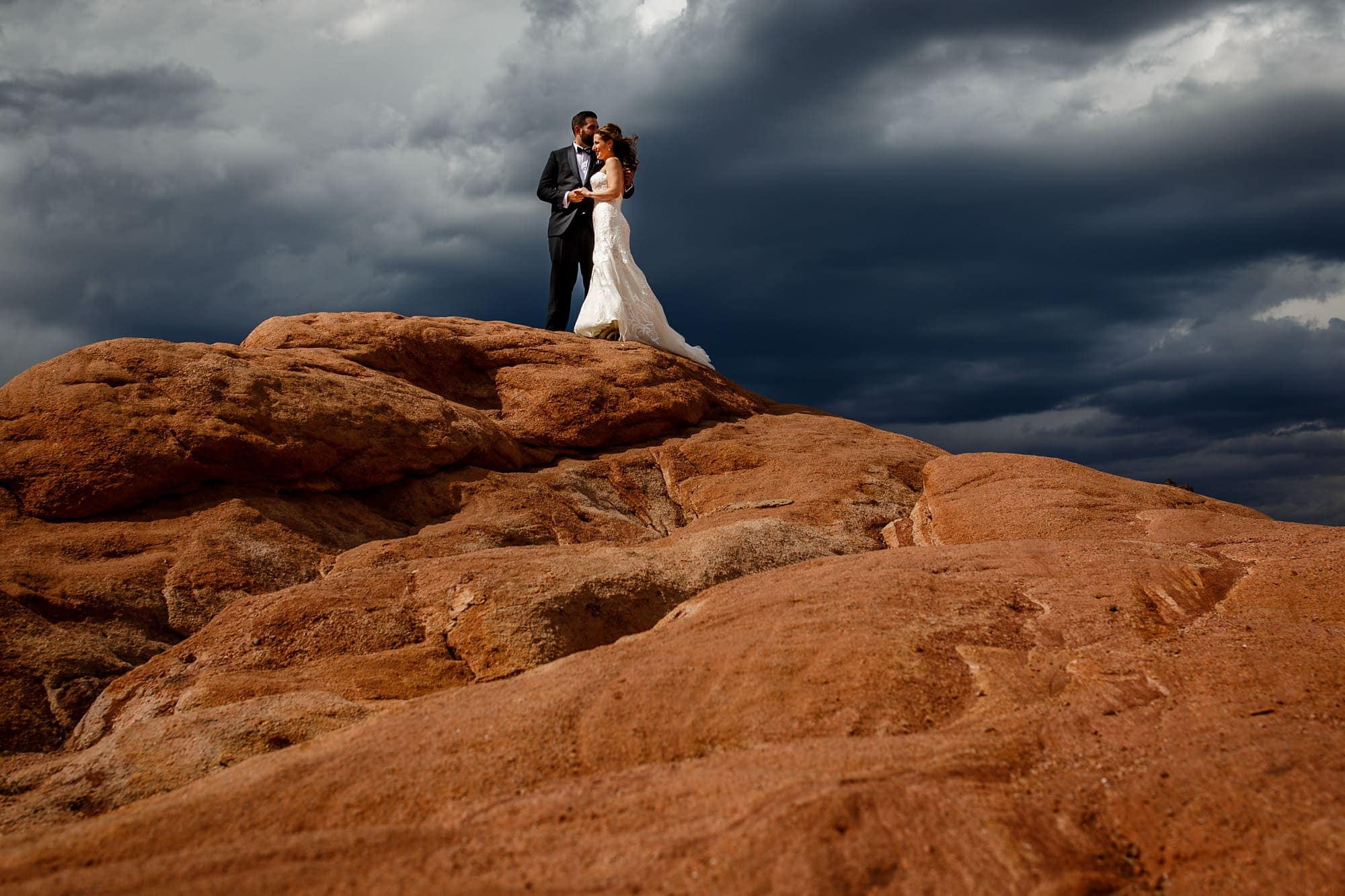 The couple share a moment on the red rocks for a portrait at Garden of the Gods park in Colorado Springs