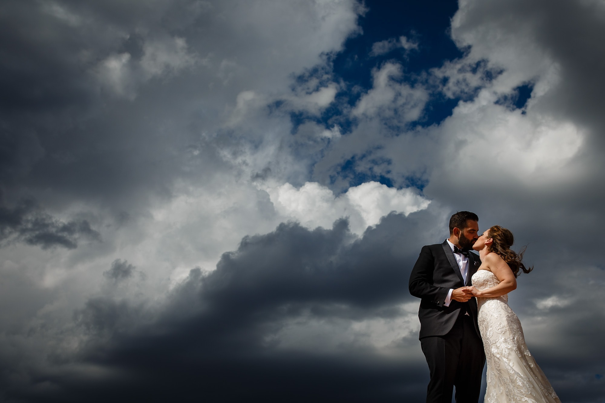 The couple share a moment beneath the clouds and sky for a portrait at Garden of the Gods park in Colorado Springs