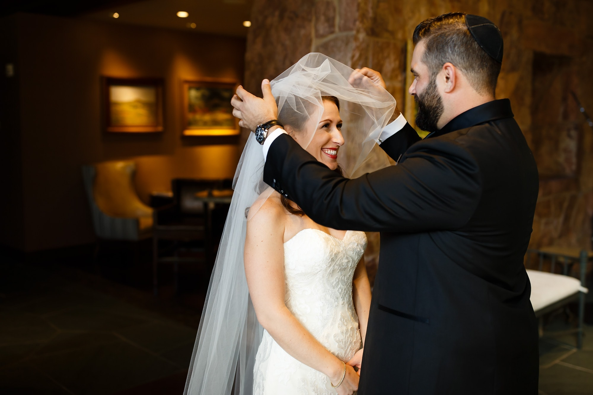 Josh veils his bride before their Jewish wedding ceremony at Garden of the Gods club