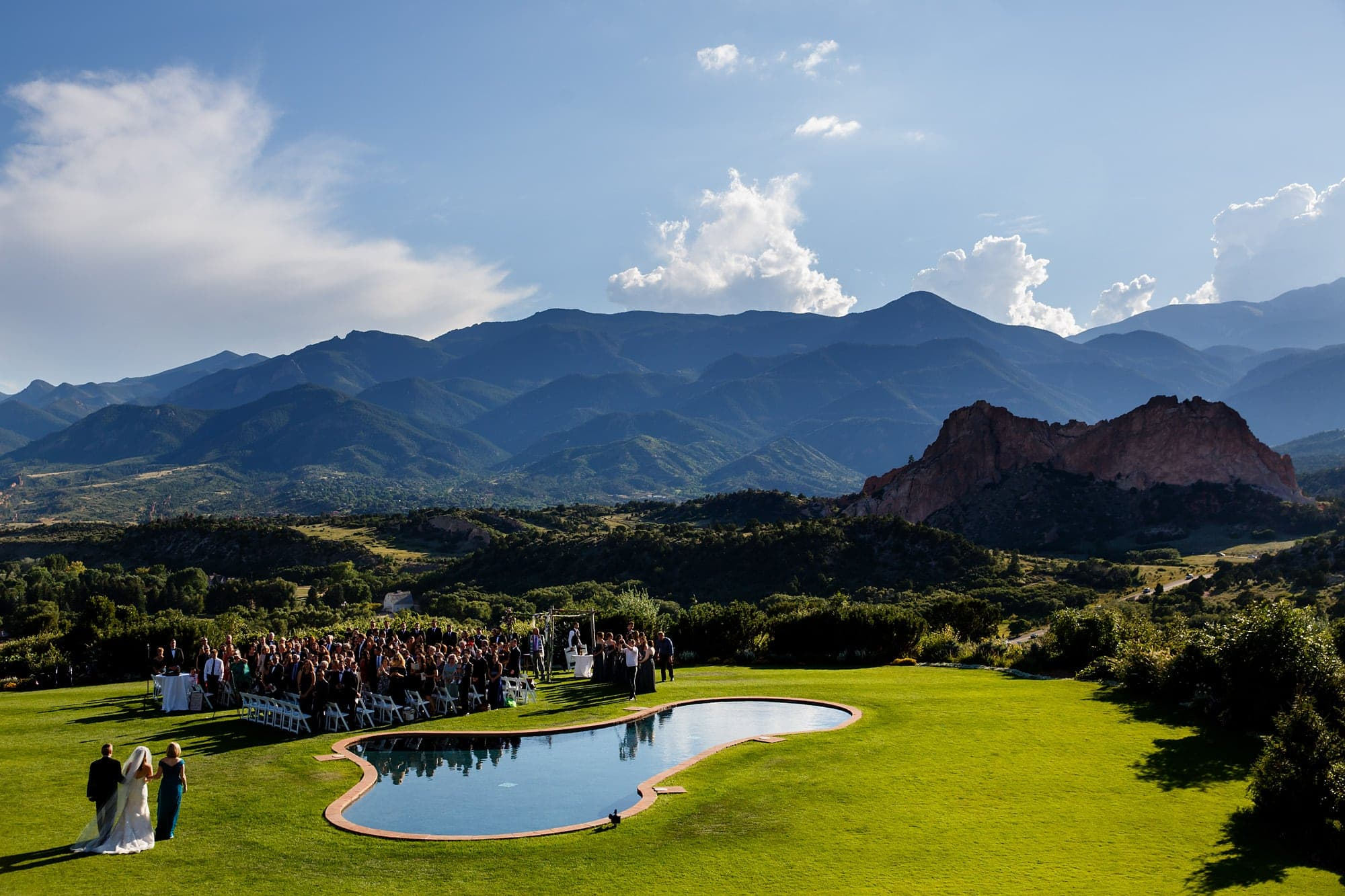 Bride Devan walks out with her parents during her summer wedding ceremony at Garden of the Gods Club in Colorado Springs near the Rocky Mountains for