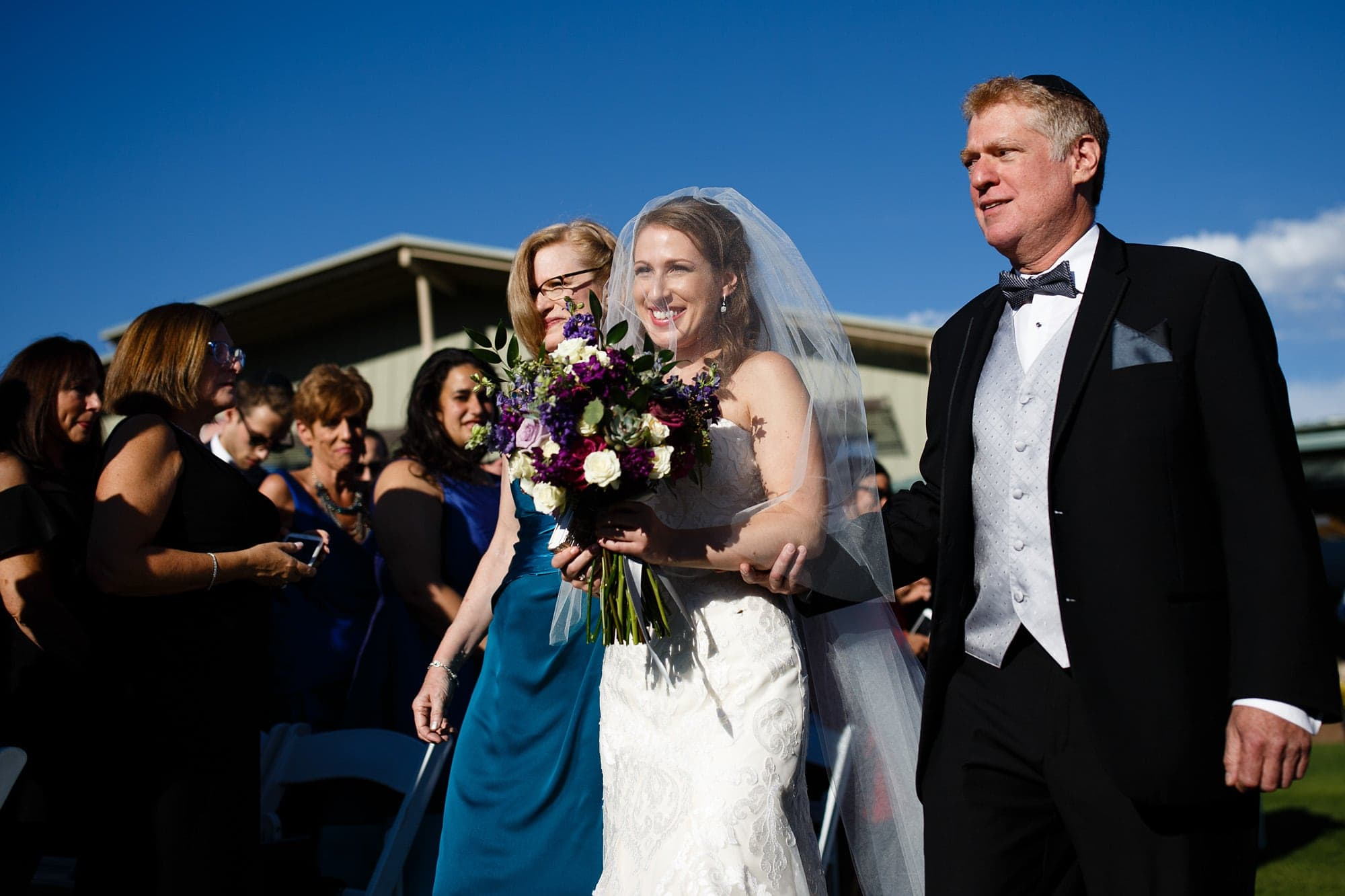 Devan walks down the aisle with her parents at Garden of the GOds Club
