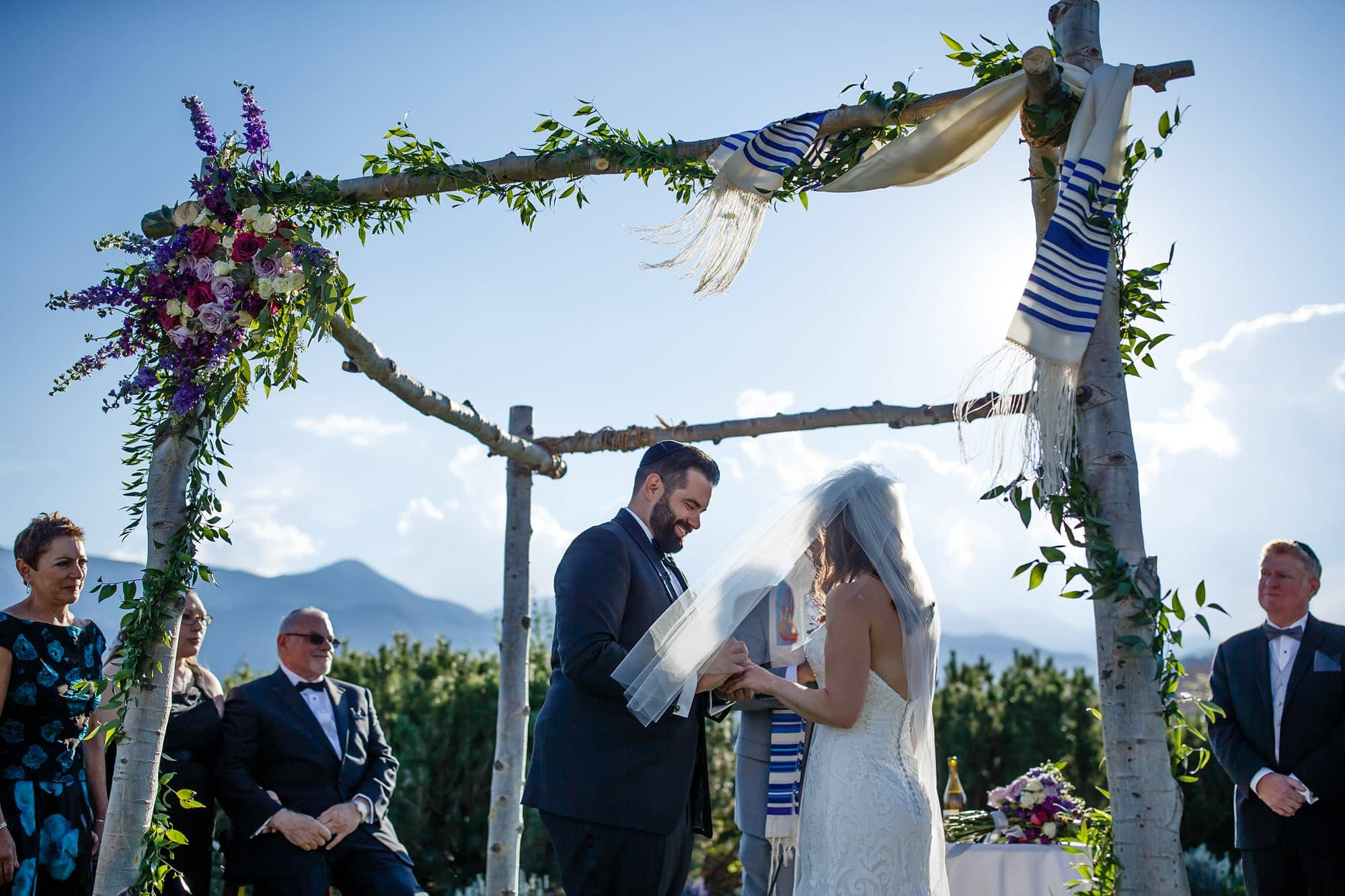 Joshua places the ring on his bride's finger under the Chuppah made of aspen trees and flowers at Garden of the Gods Club in Colorado Springs