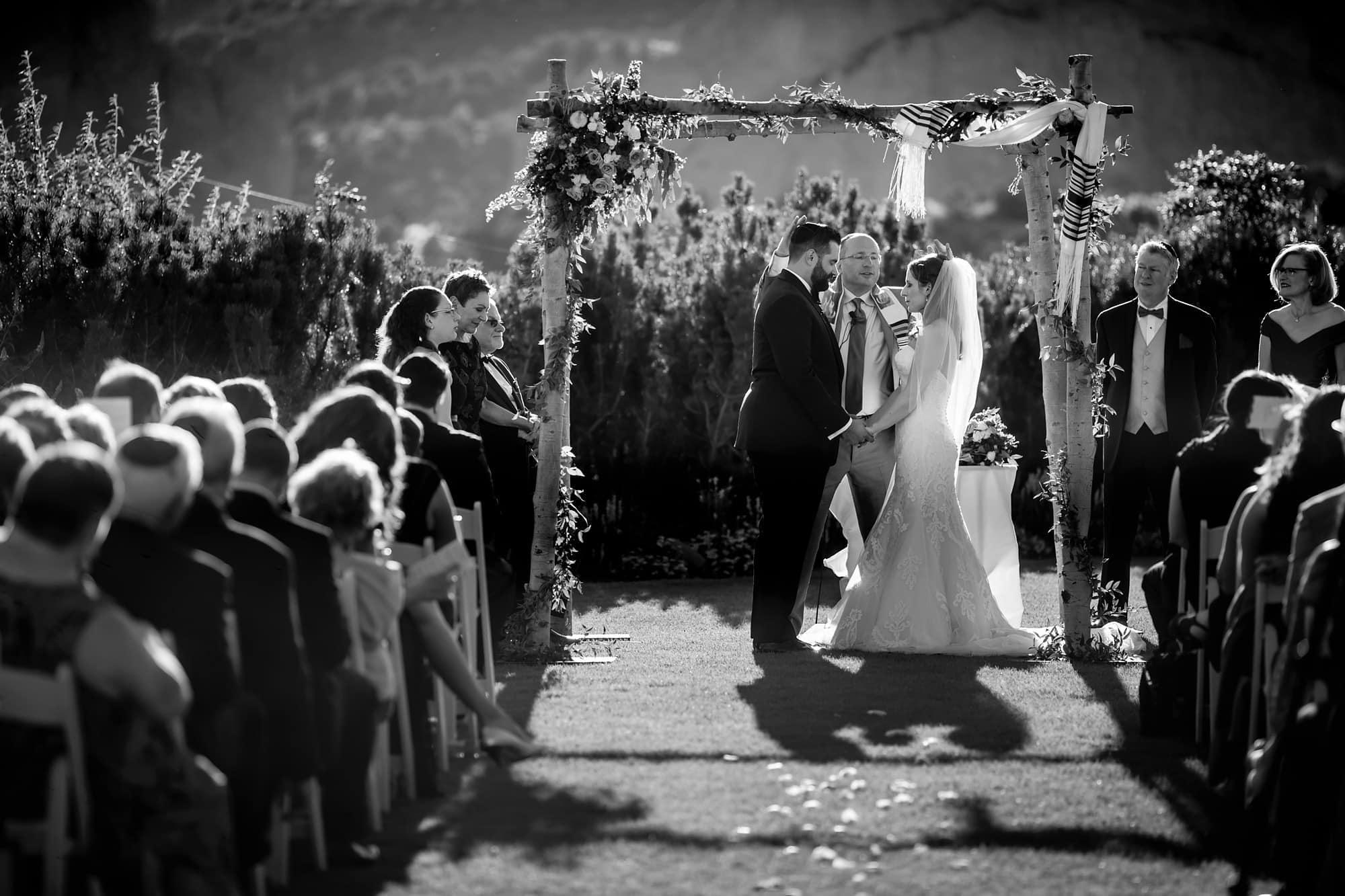 The rabbi prays during the jewish wedding ceremony at Garden of the Gods Club