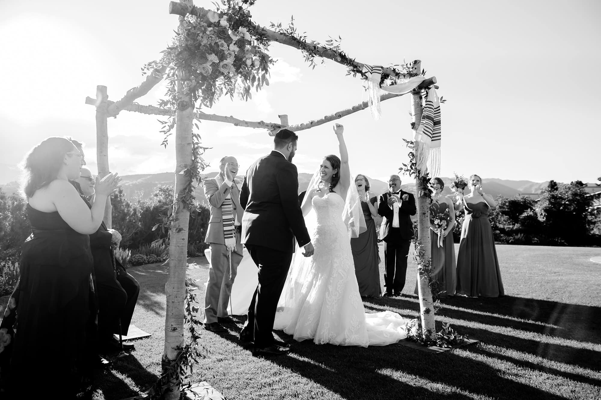 The bride celebrates under the chuppah made of aspen trees at Garden of the Gods Club in Colorado Springs