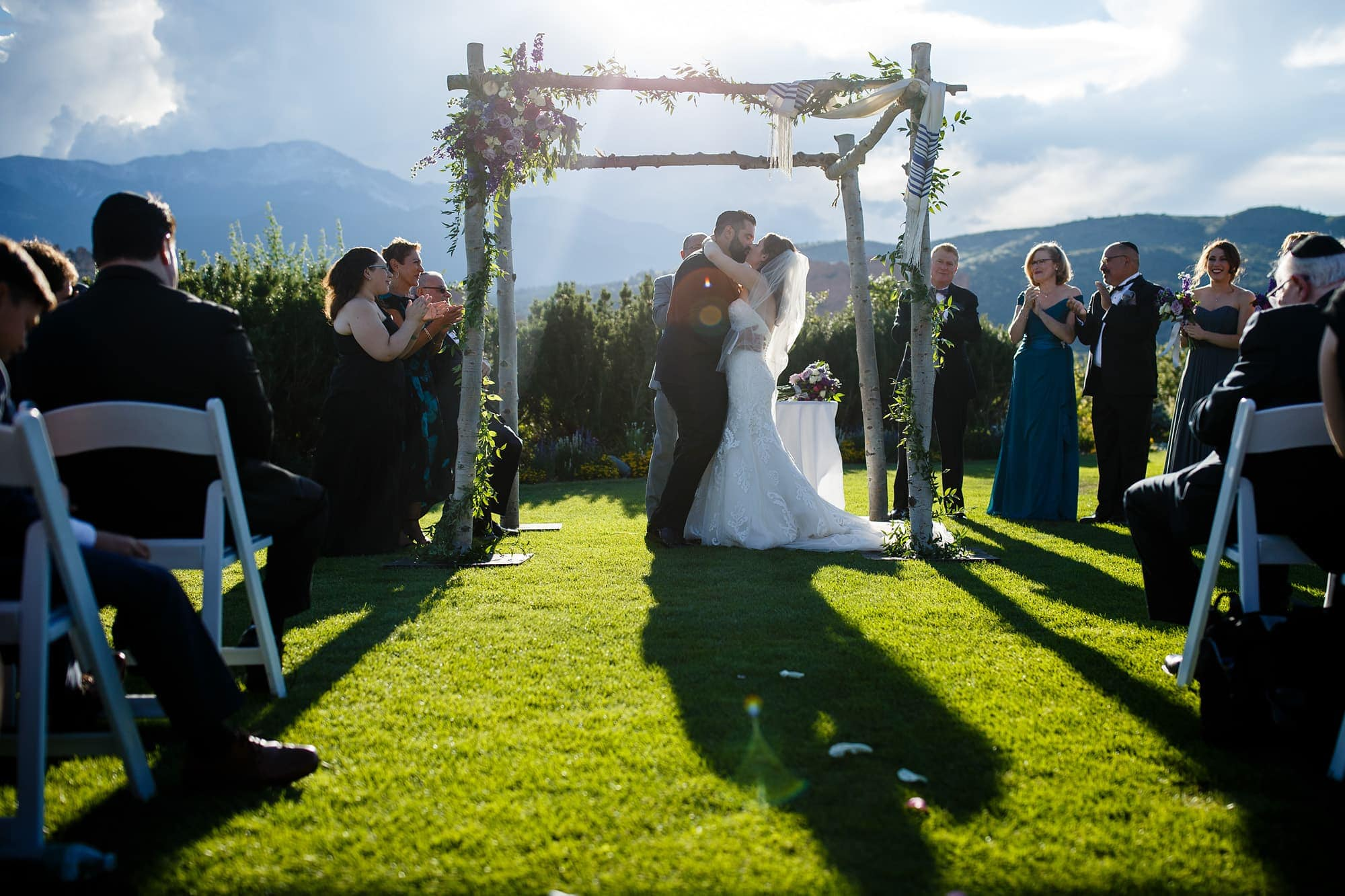Devan and Joshua share their first kiss together under the chuppah made of aspen trees and flowers during their Jewish summer ceremony at Garden of the Gods Club