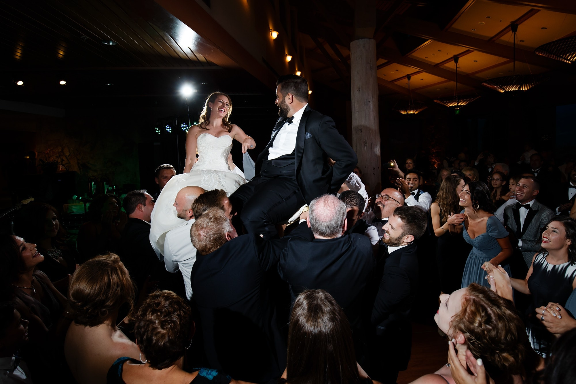 Devan and Joshua are raised on chairs during the horah dance at their wedding reception at Garden of the Gods Club