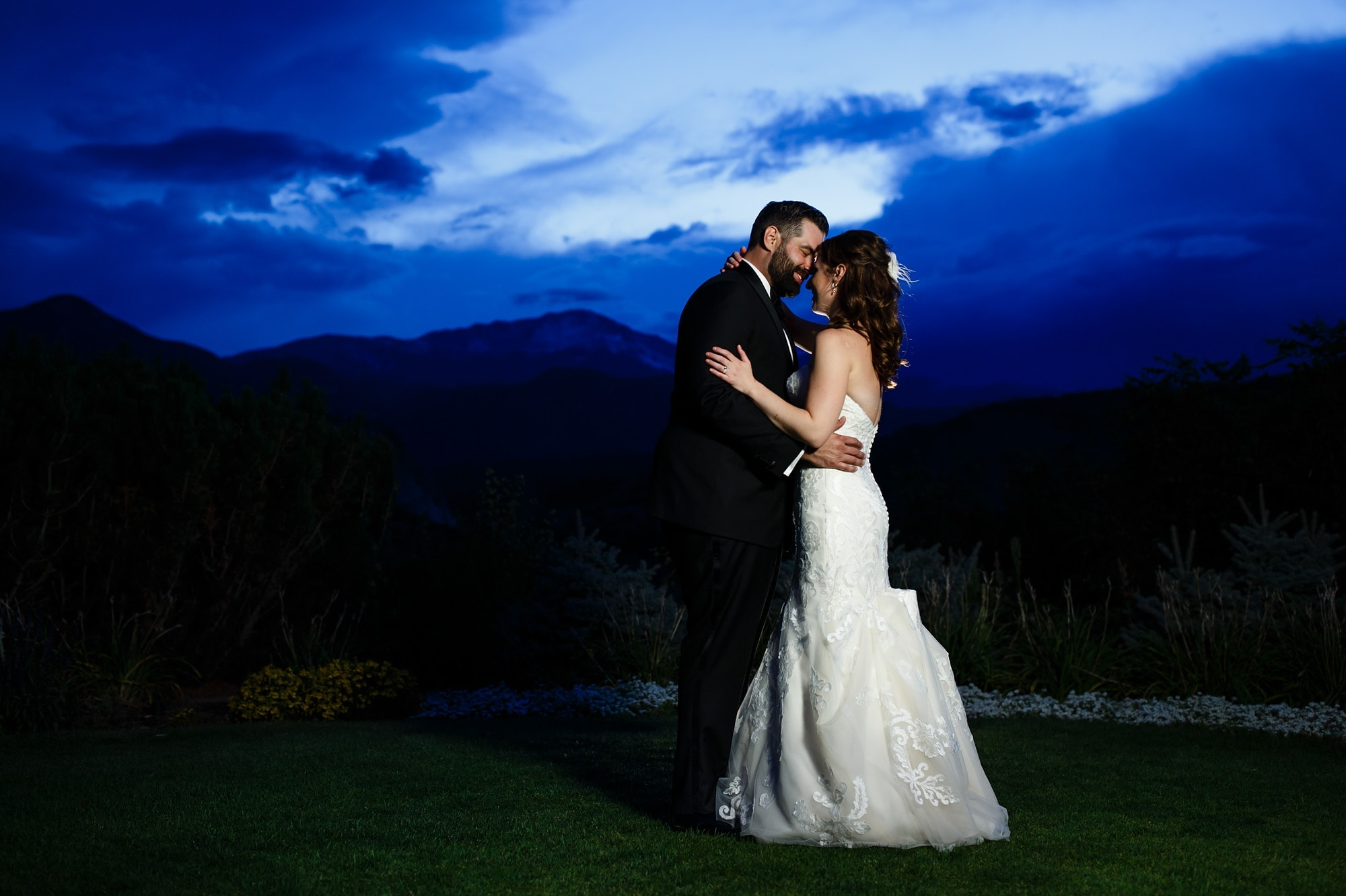 Devan and Joshua share a moment togehter outsude during twilight in front of Pikes Peak during their wedding at Garden of the Gods Club