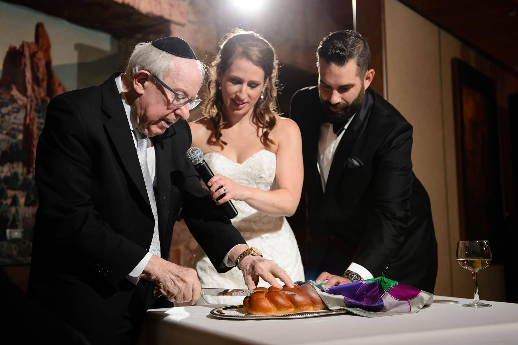 Devan's grandfather cuts the challah