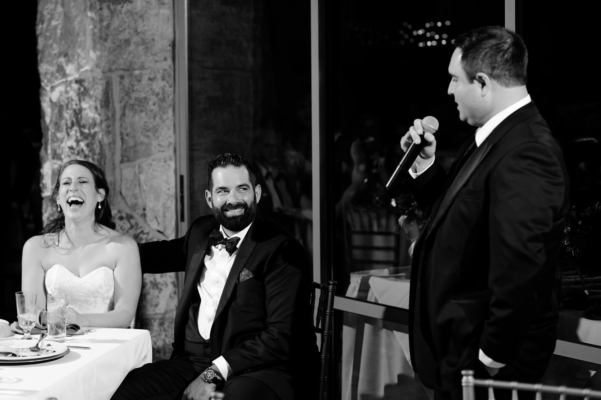 The couple laughts during a speech from the best man