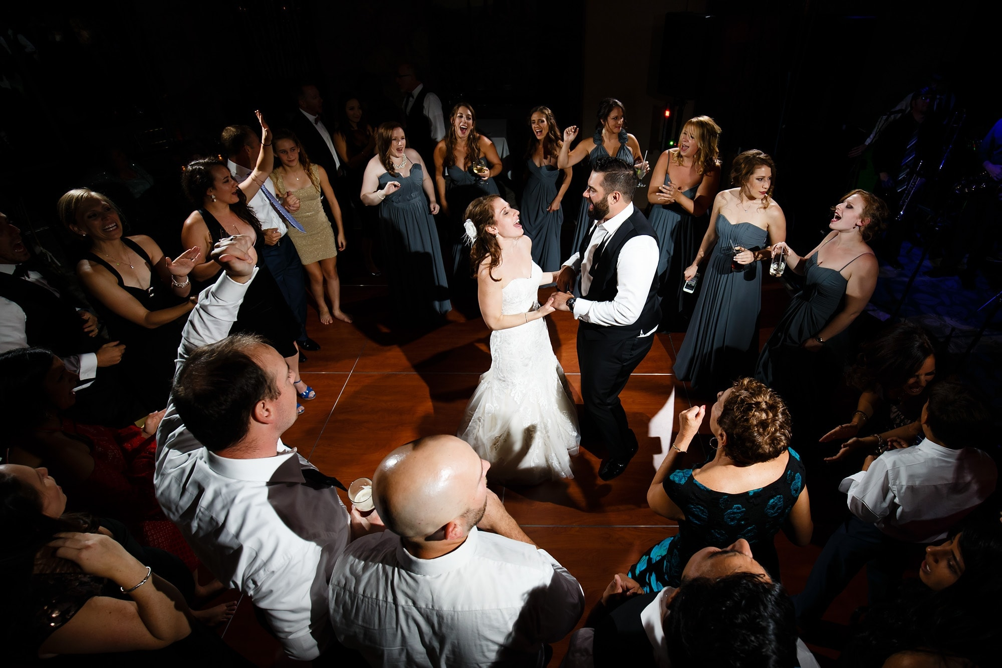 The bride and groom dance with all their friends and family during their wedding reception at Garden of the Gods Club