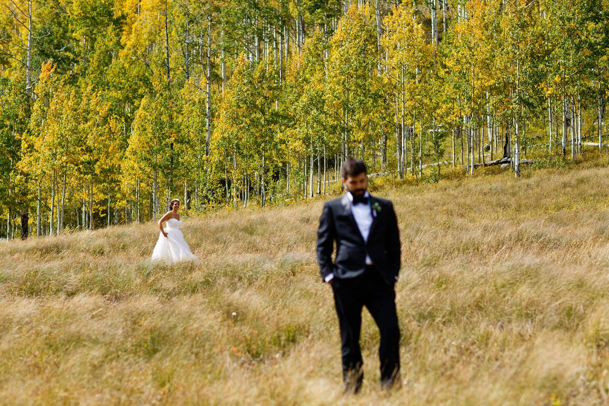 Becky walks towards Brian before their first look as the aspen trees are full of color at Piney River Ranch.
