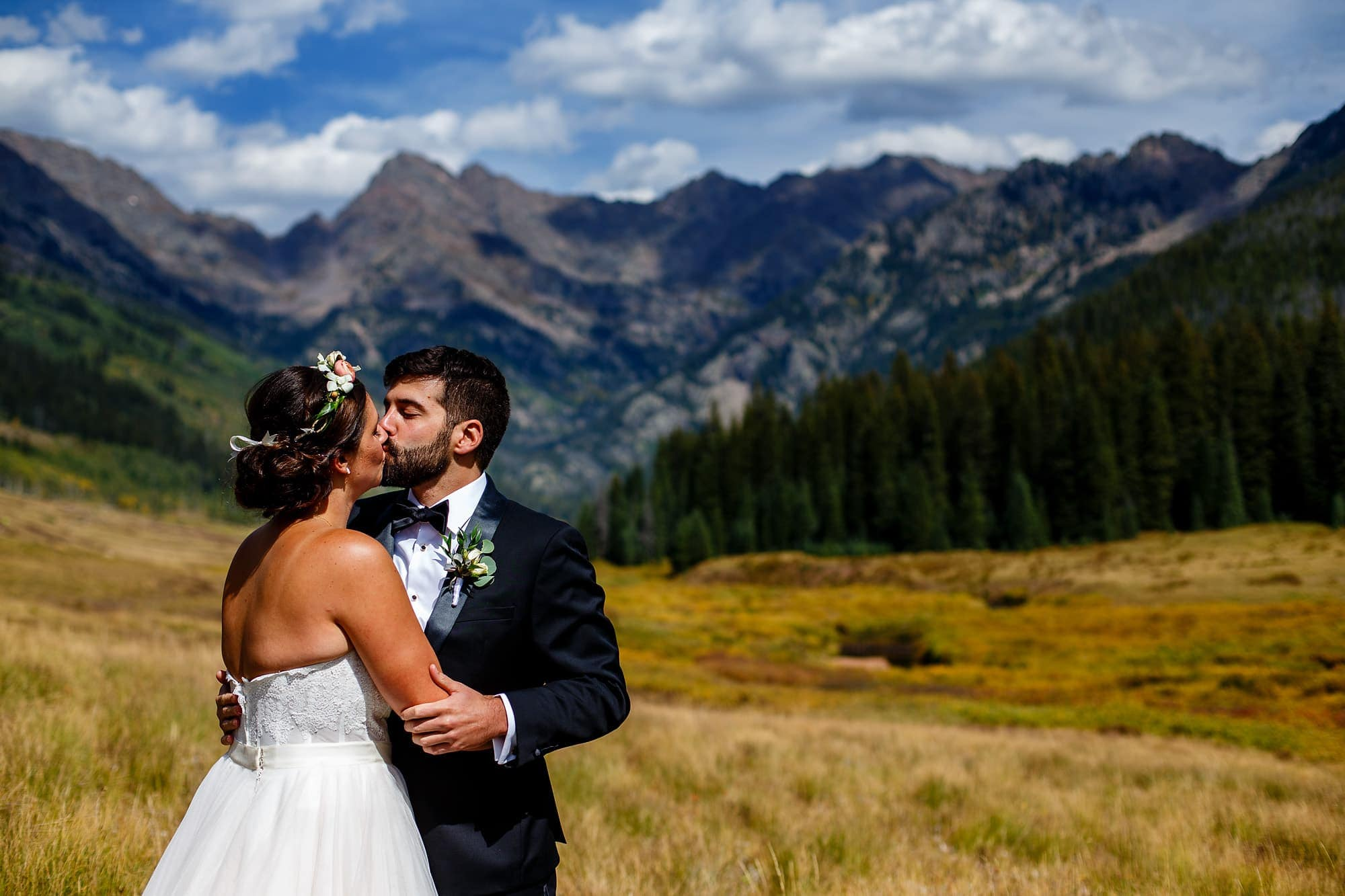 Becky and Brian kiss in front of the Gore Mountain Range outside of Vail.