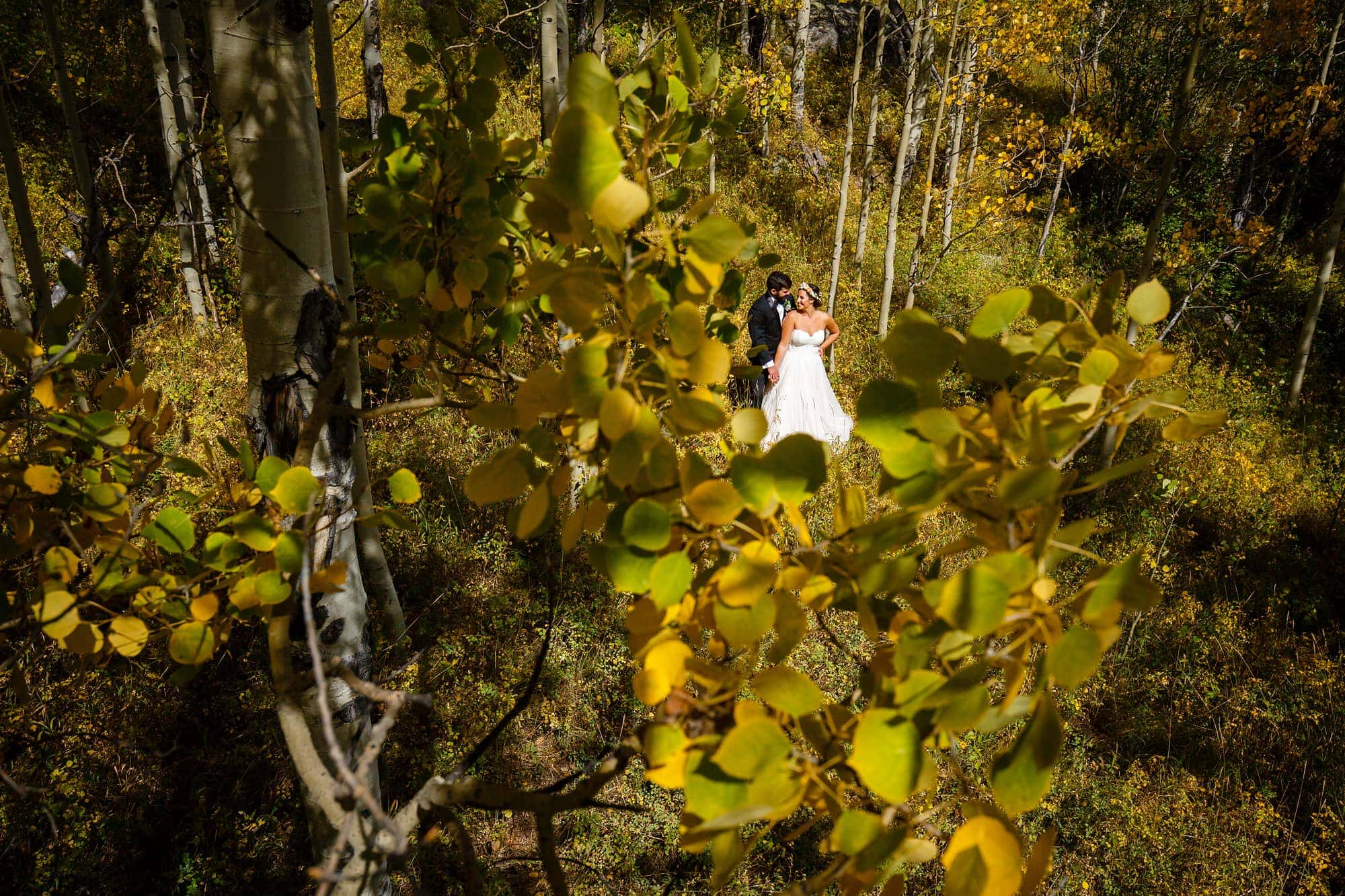 Becky and Brian are surrounded by yellow aspen leaves in September at Piney River Ranch for a portrait.