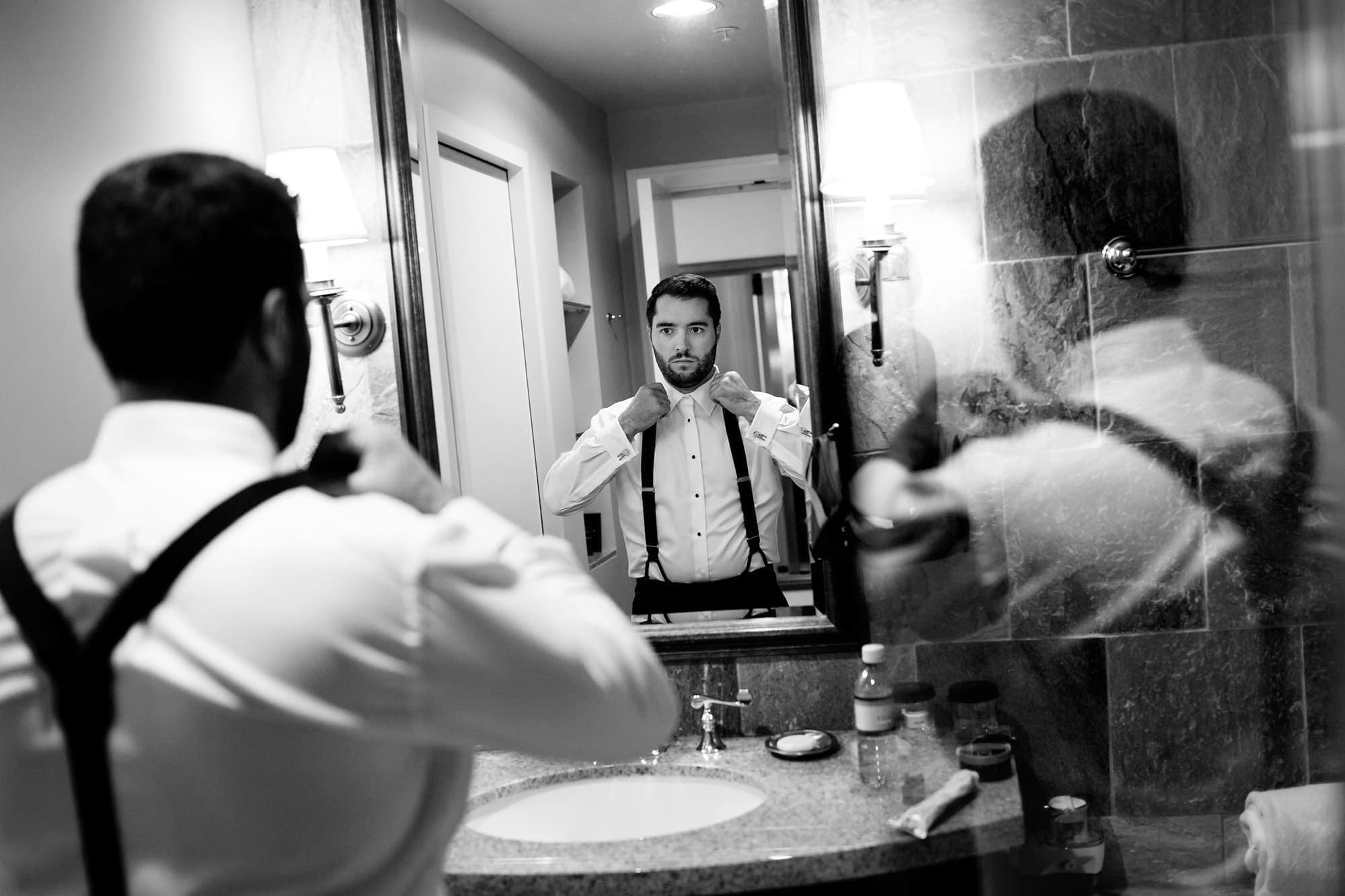 Bryan adjusts his suspenders at the St. Julien Hotel in Boulder before his wedding