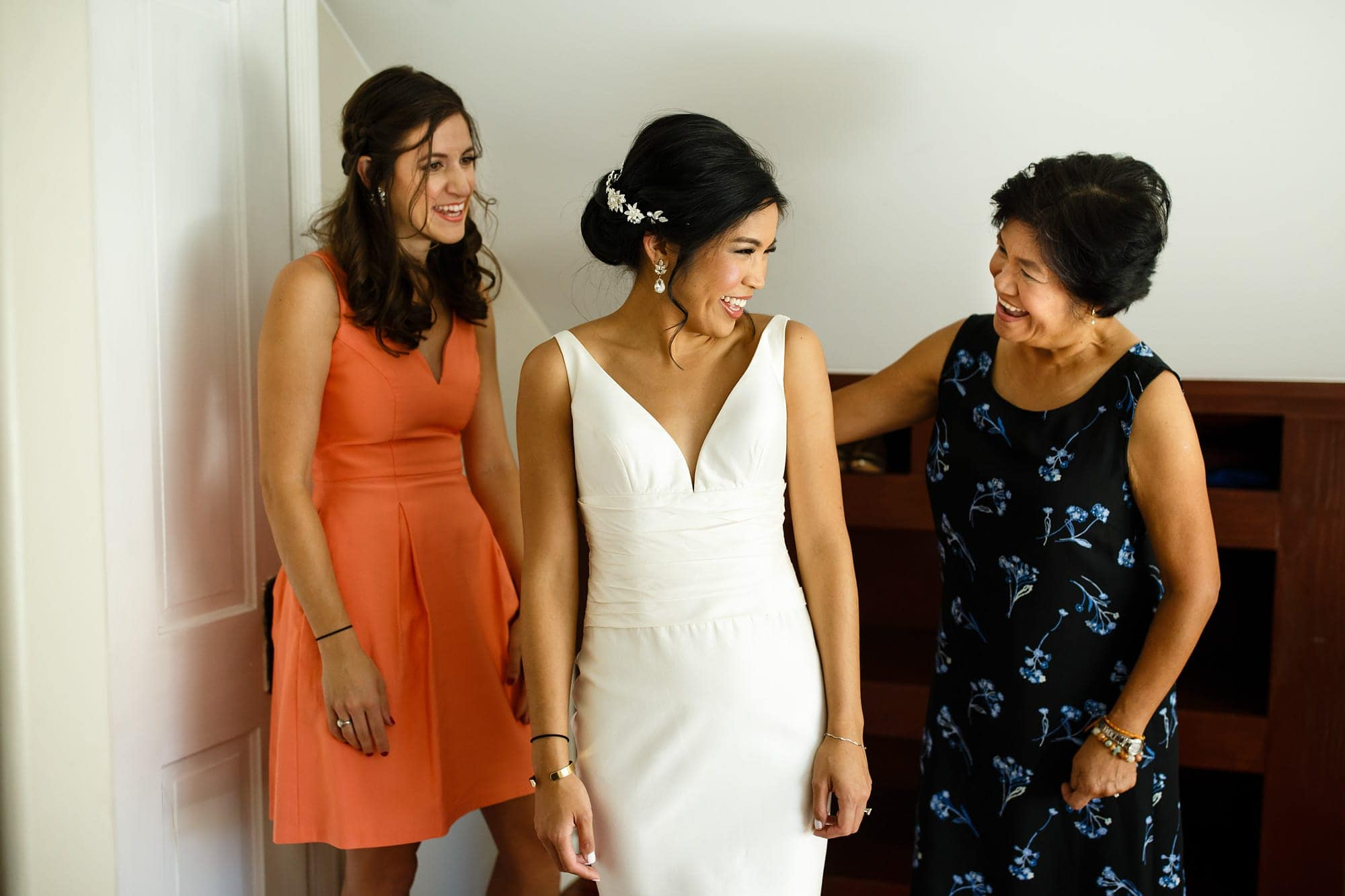 Megan shares a laugh with her mother while getting dressed with her maid of honor before her wedding in Boulder at Rembrandt Yard