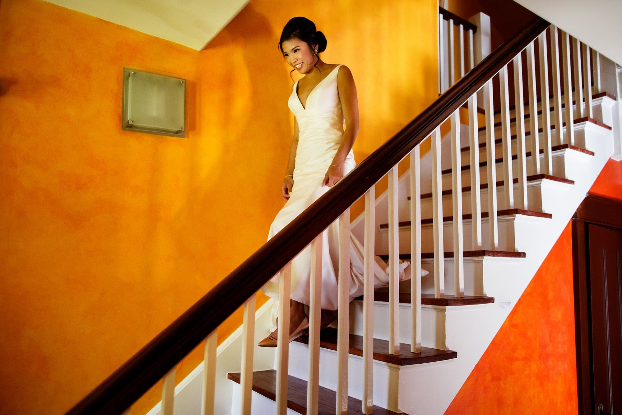 Megan walks down the stairs for the first time in her wedding dress at an Air BnB home in Boulder