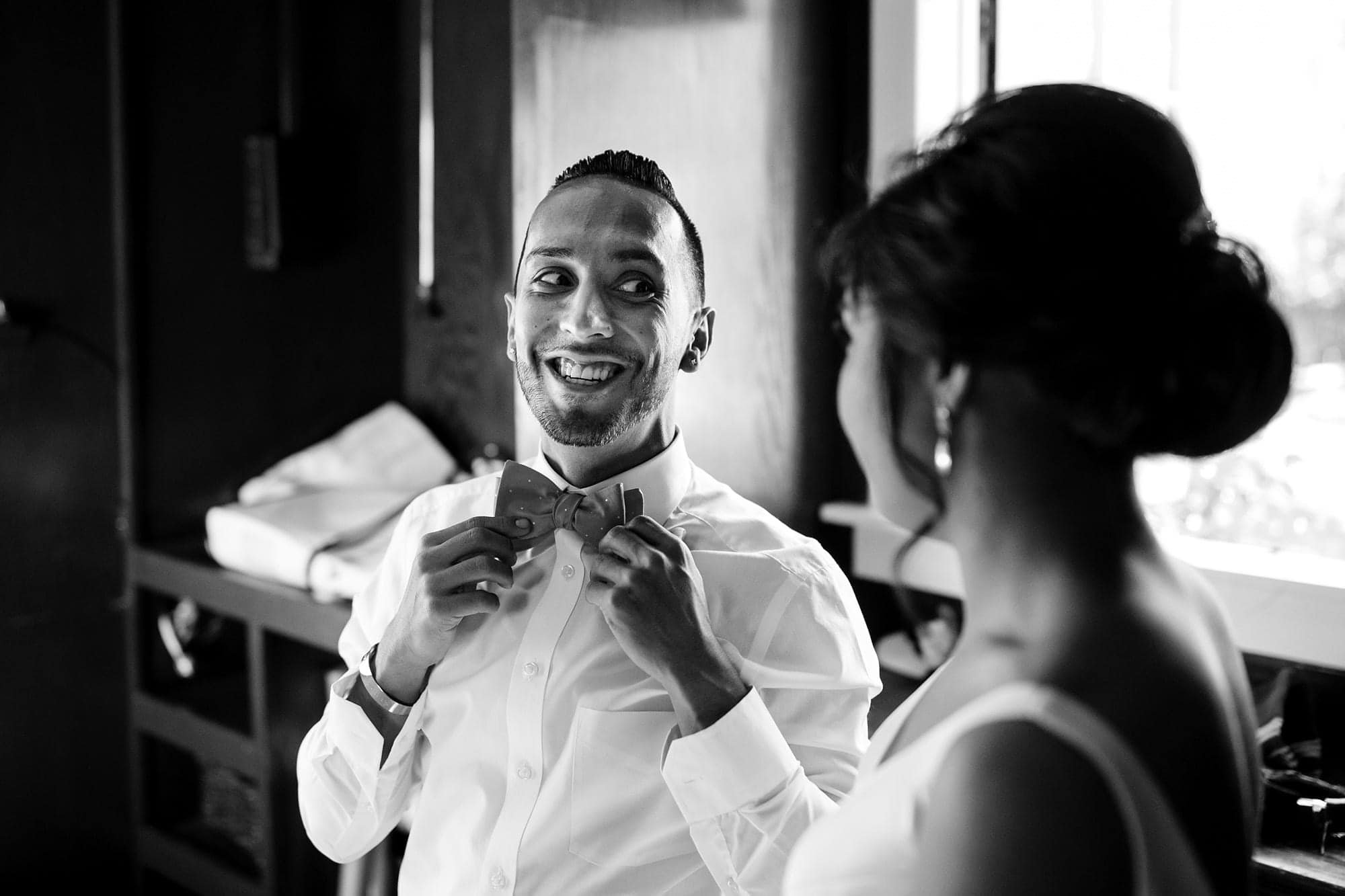 A friend adjusts his bow tie while laughing with the Bride
