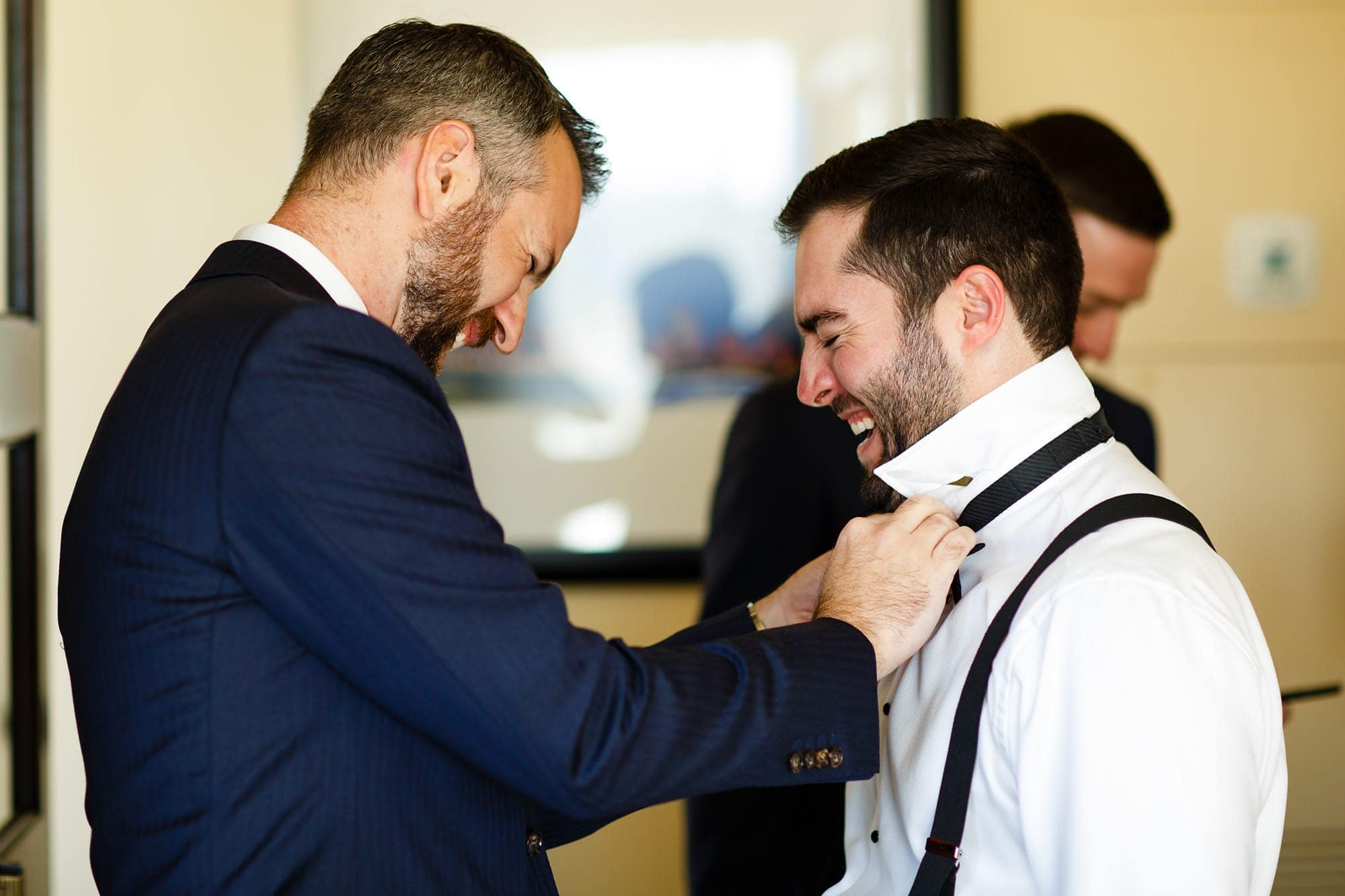 Bryan laughs while getting help with his tie at the St. Julien Hotel in Boulder