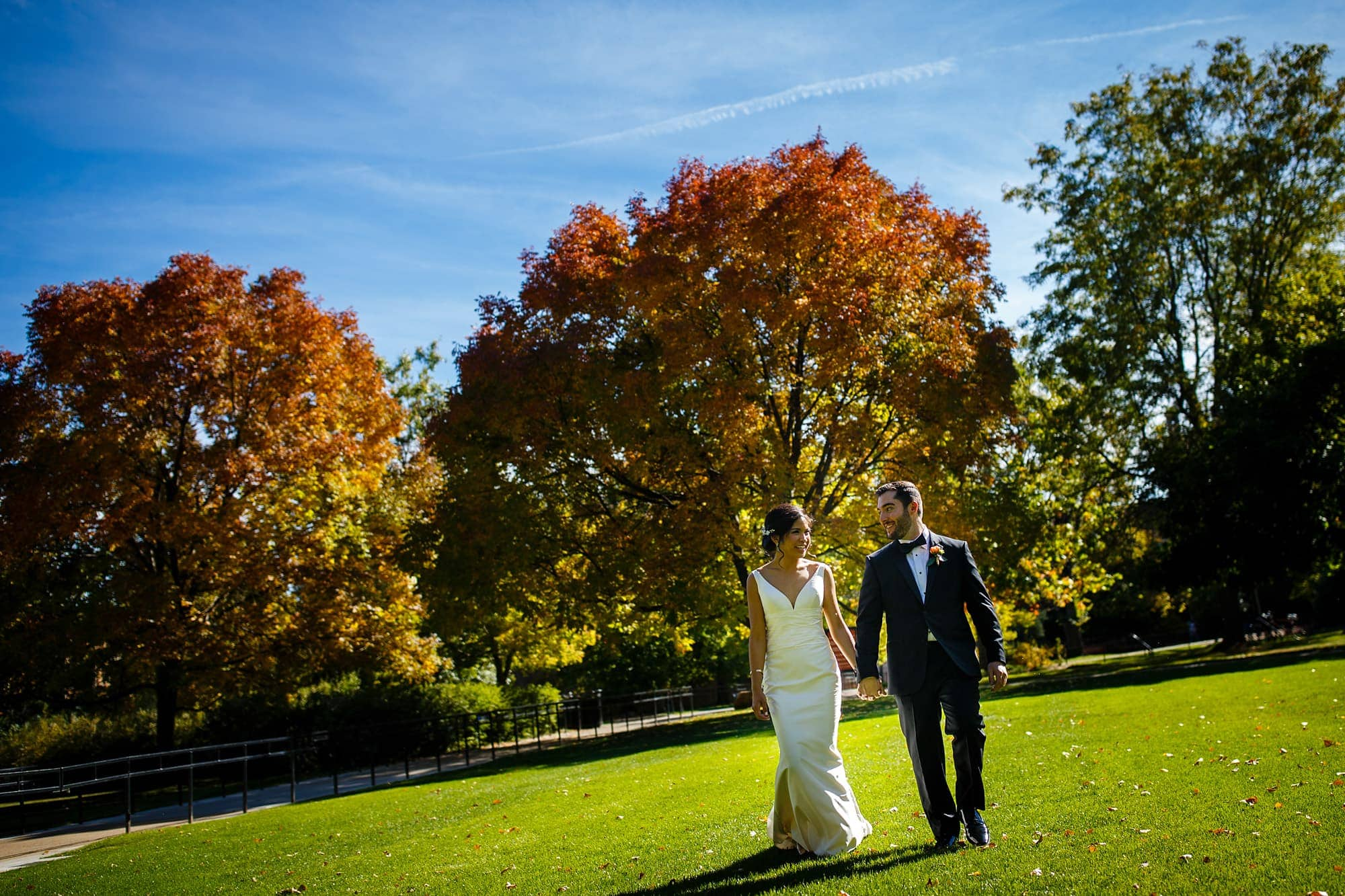 Megan and Bryan walk on Norlin Quad on the University of Colorado campus before their fall wedding