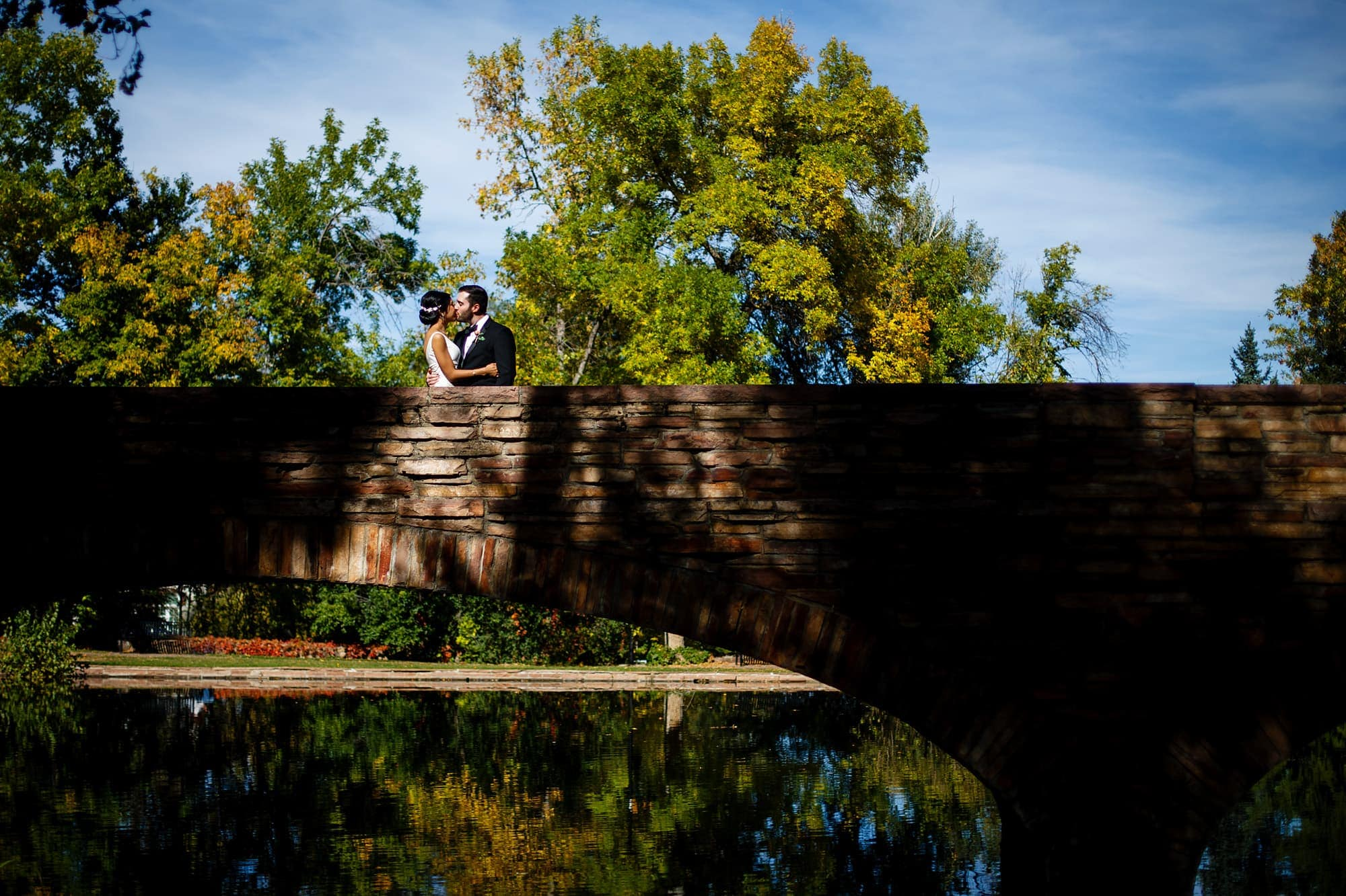 Megan and Bryan kiss onthe Varsity Lake Bridge on the University of Colorado campus before their wedding