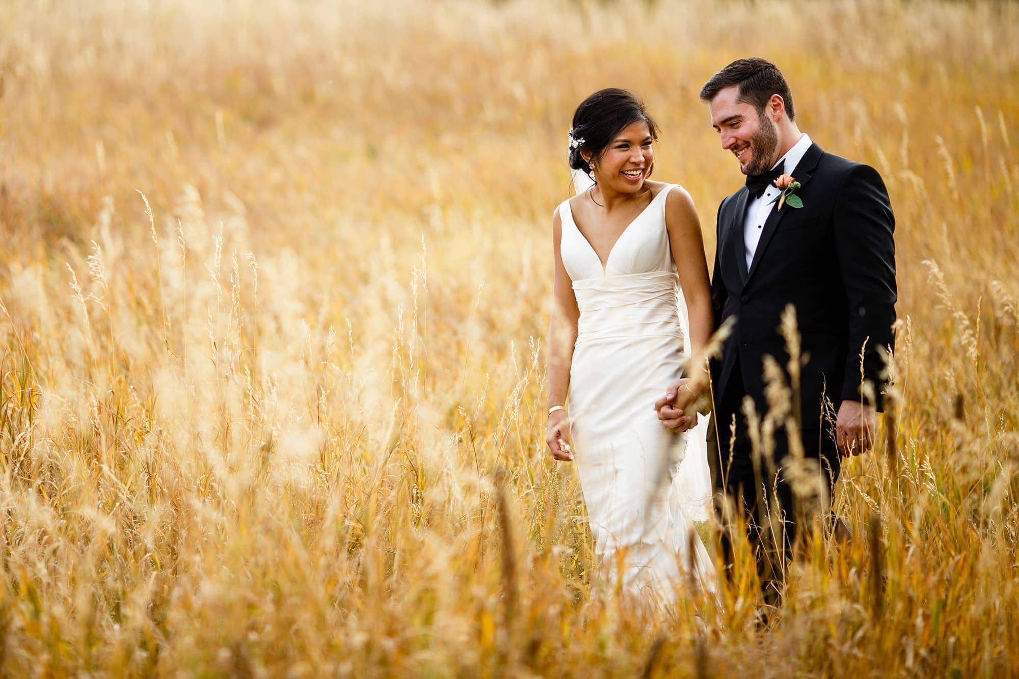 Megan walks with Bryan in the long grass at Centennial Park Trailhead in Boulder following their fall wedding