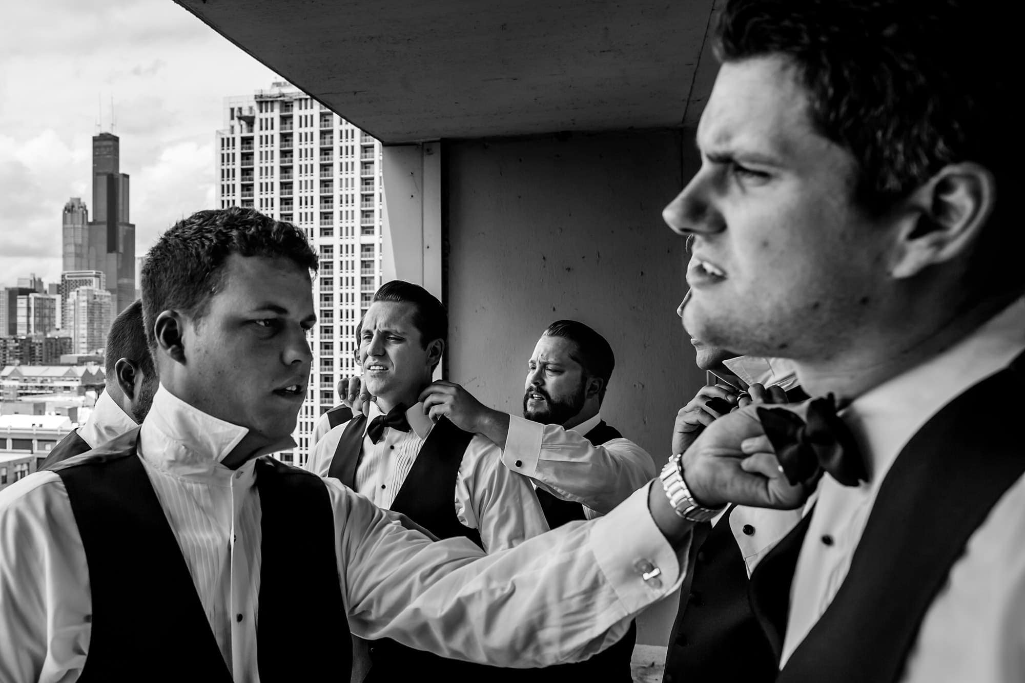 The groom and his groomsmen help adjust each others bowtie while getting ready at a condo in the South Loop of Chicago as Willis Tower is seen in the background.