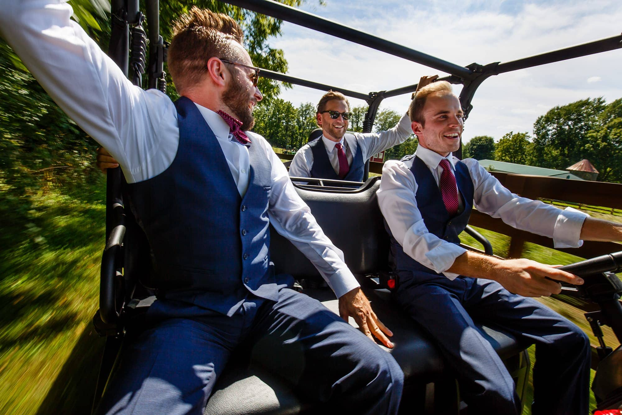 Groomsmen ride in an ATV around a farm near Willow Harbor Vineyards in Three Oaks, Michigan in Spetember.