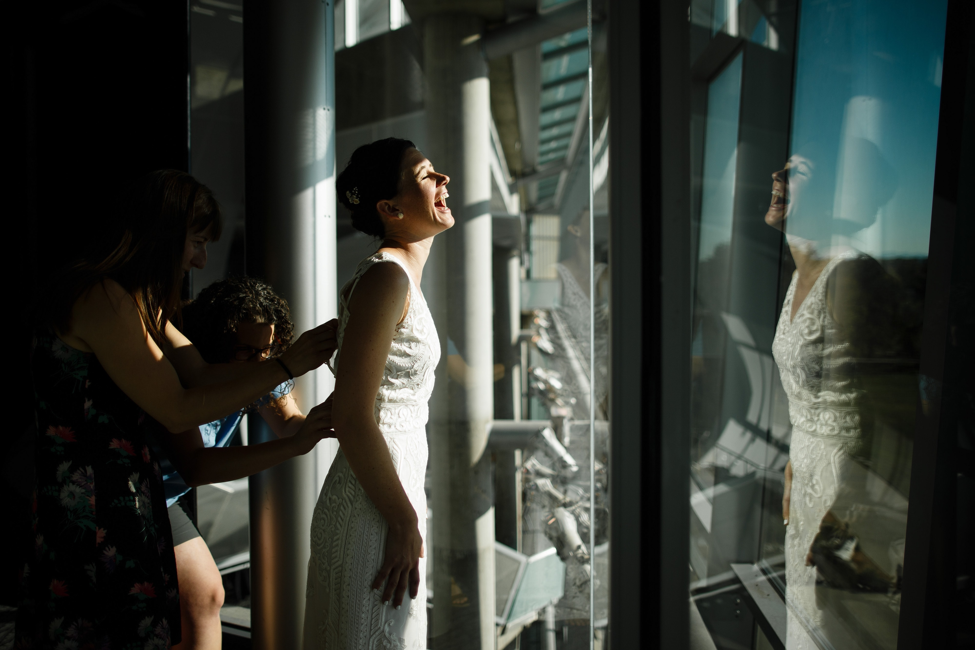 A bride shares a laugh while getting into her dress before her wedding at the Denver Museum of Nature and Science