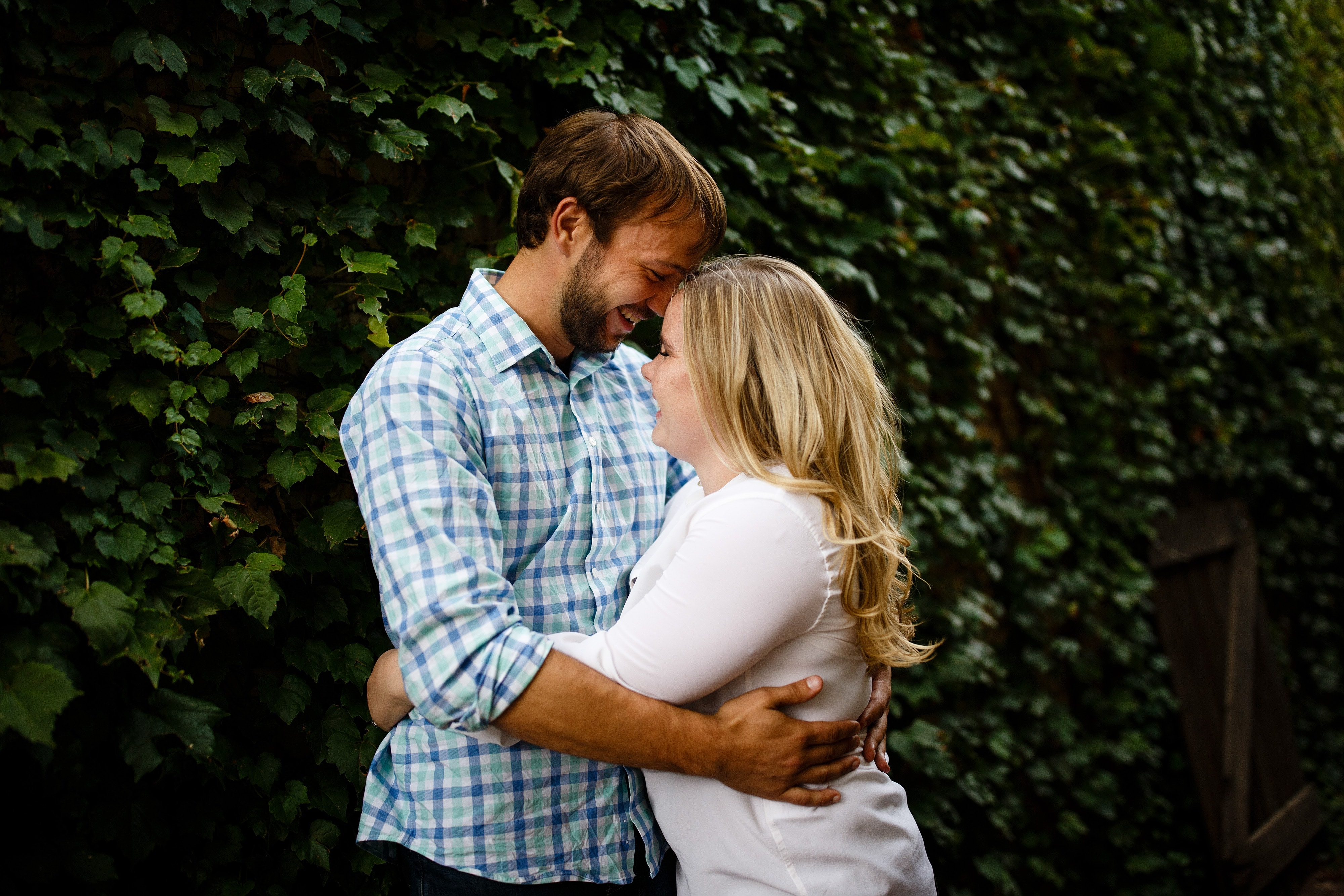 Joel and Coza embrace in an ivy covered alley near downtown Golden Colorado