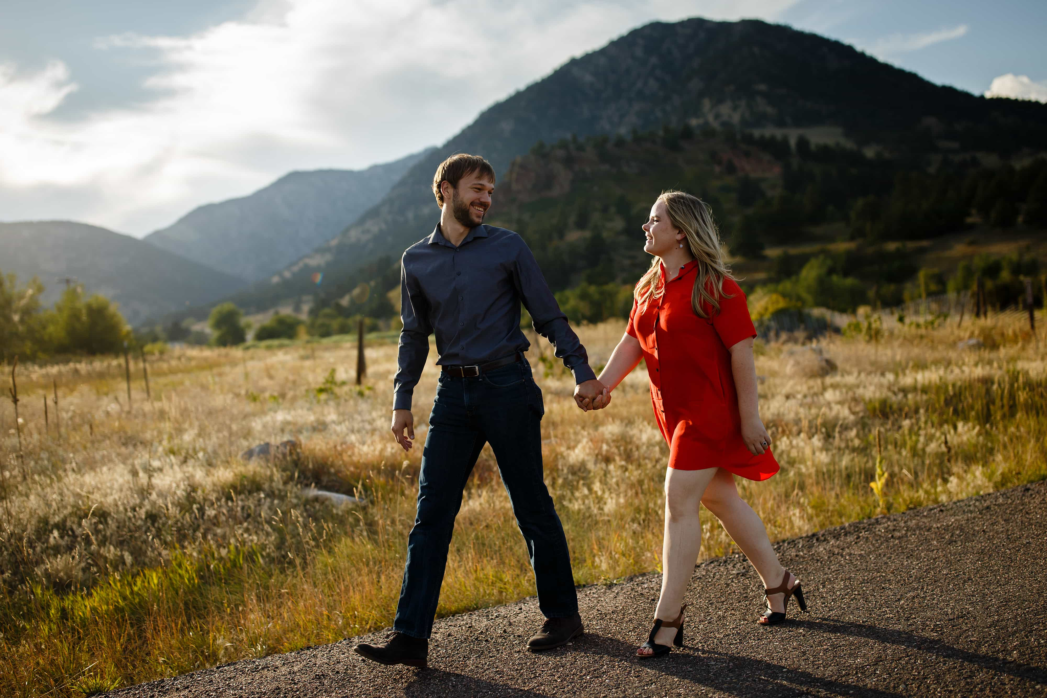 Coza wears a red dress during her engagement photos with Joel near Coal Creek Canyon during fall in Colorado