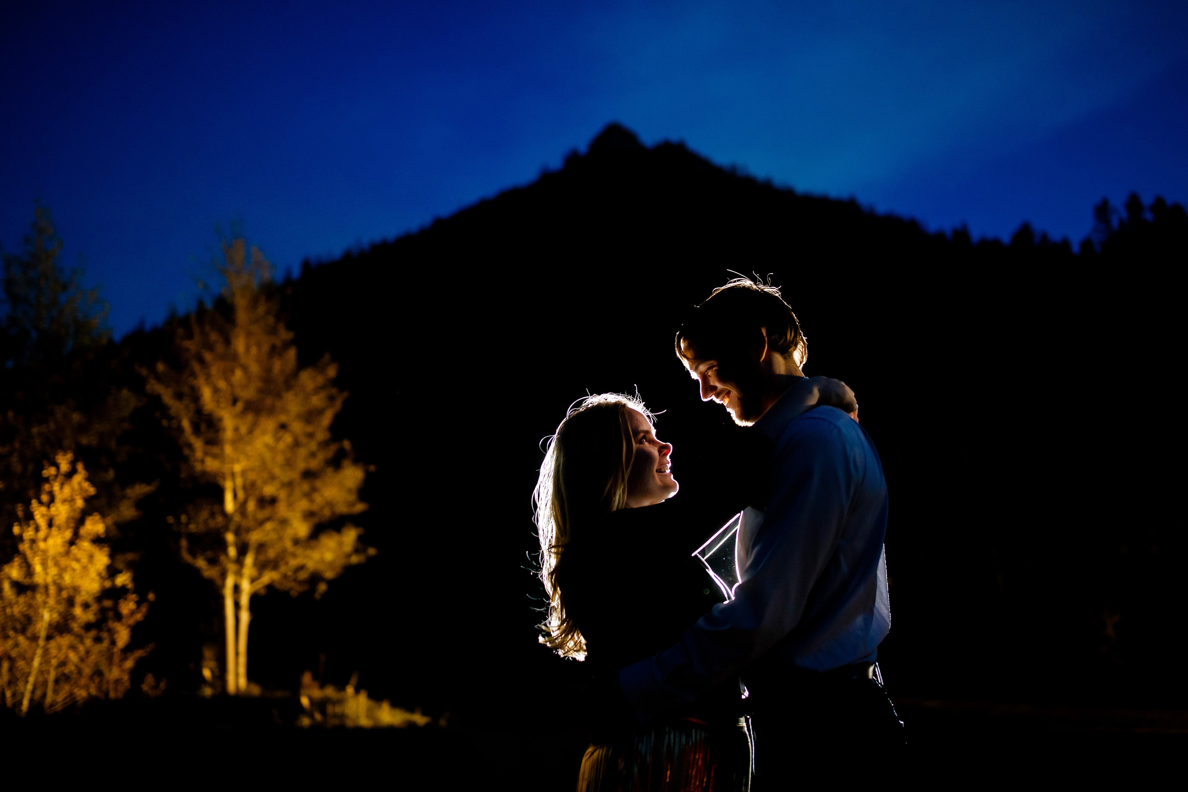 Coza and Joel are illuminated near a grove of aspen trees at twilight during their fall Golden engaement at Golden Gate Canyon State Park