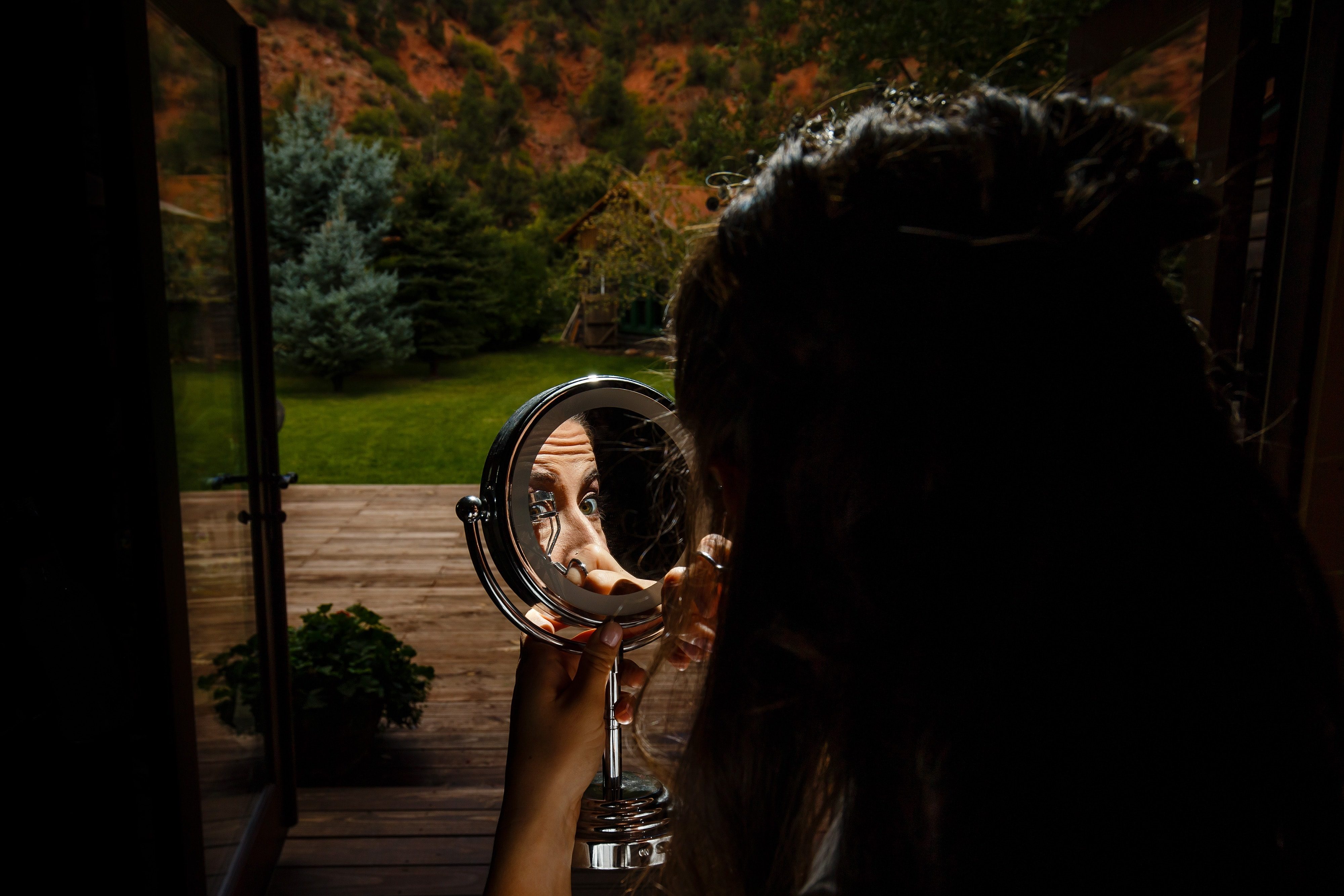 Mallory crimps her eyelashes before her Snowmass Cottages wedding