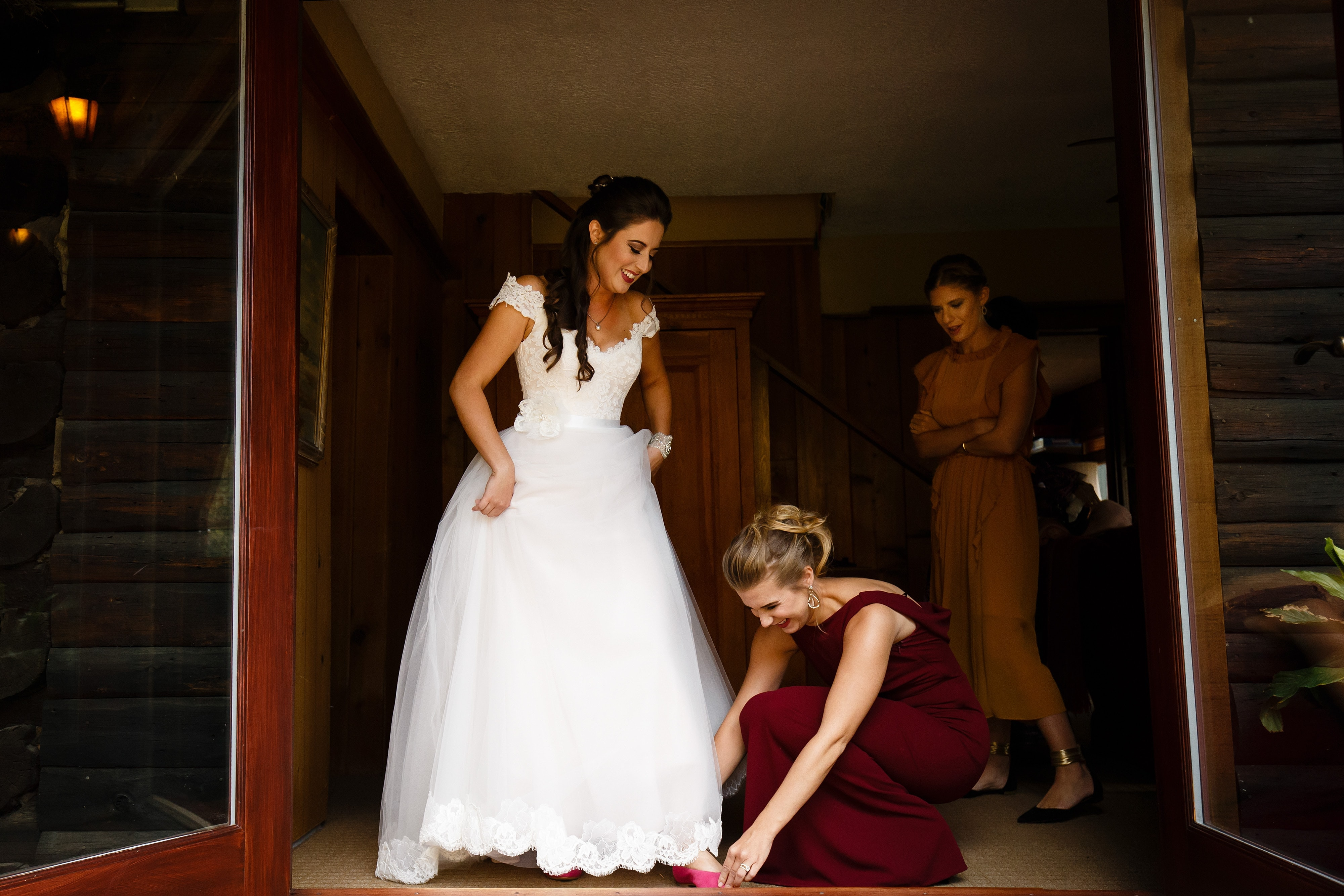 Mallory's sister helps her get into her shoes on her wedding day at Snowmass Cottages