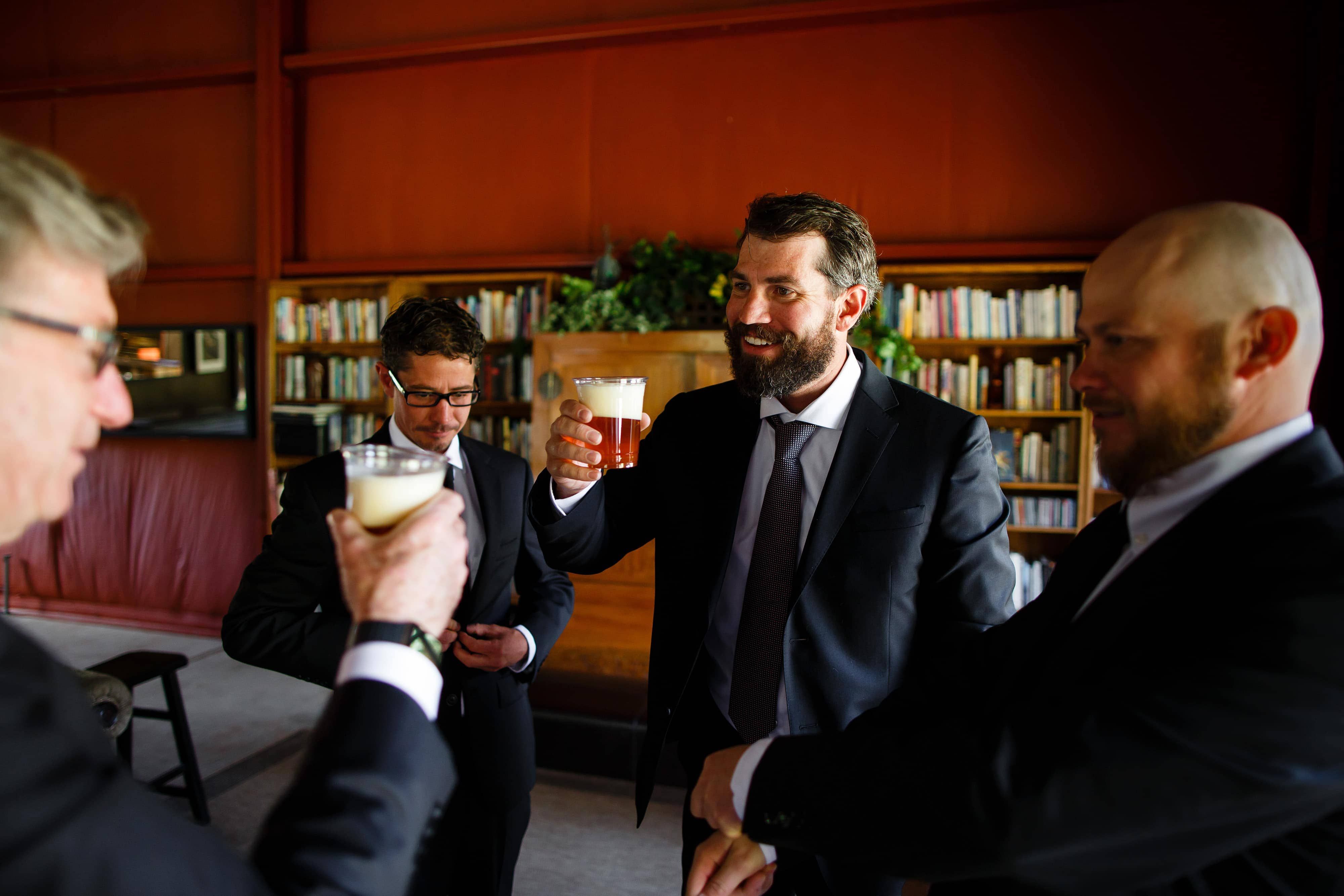 The groom shares a beer with family on his wedding day at Snowmass Cottages