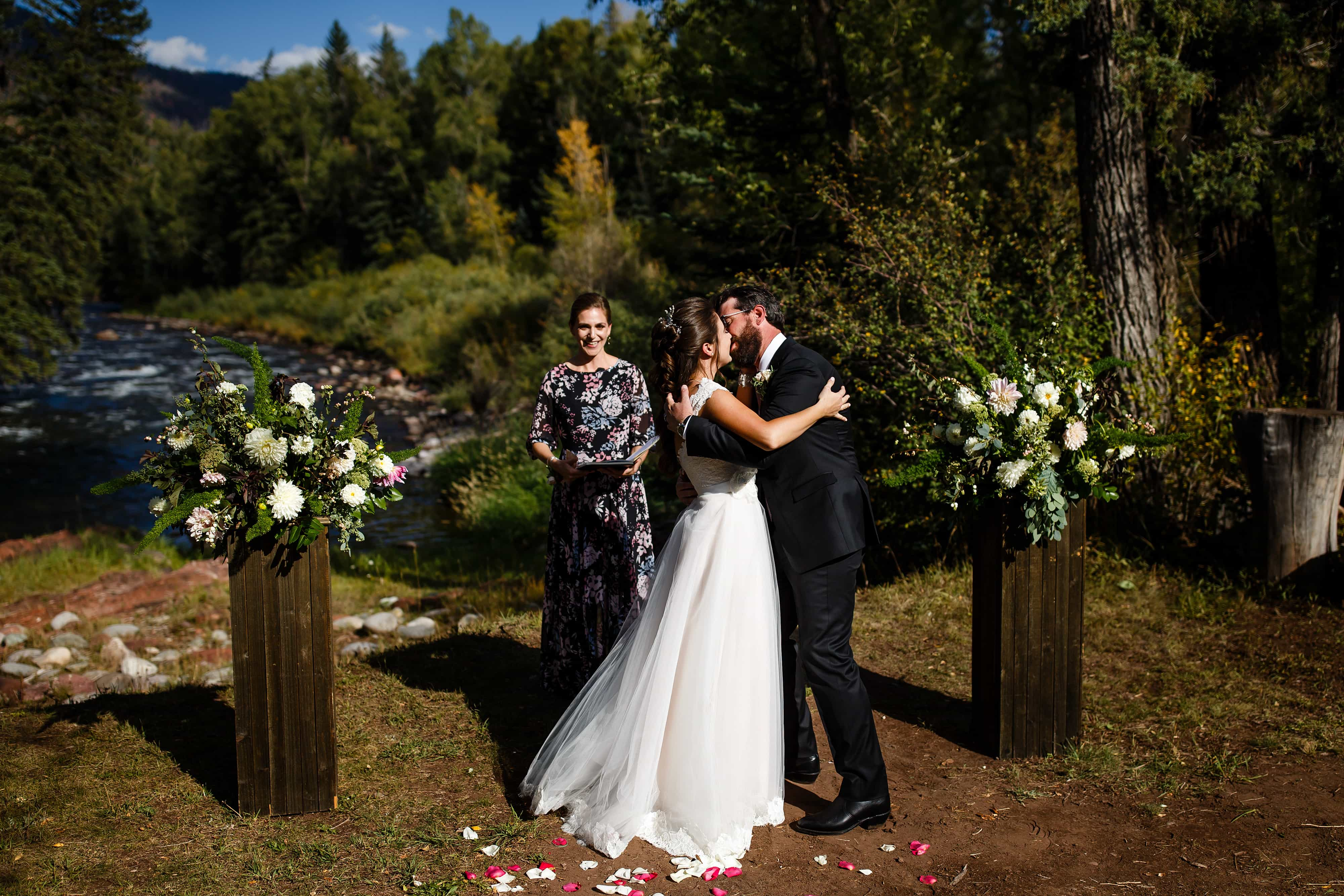The groom kisses the bride during their wedding ceremony at Snowmass Cottages
