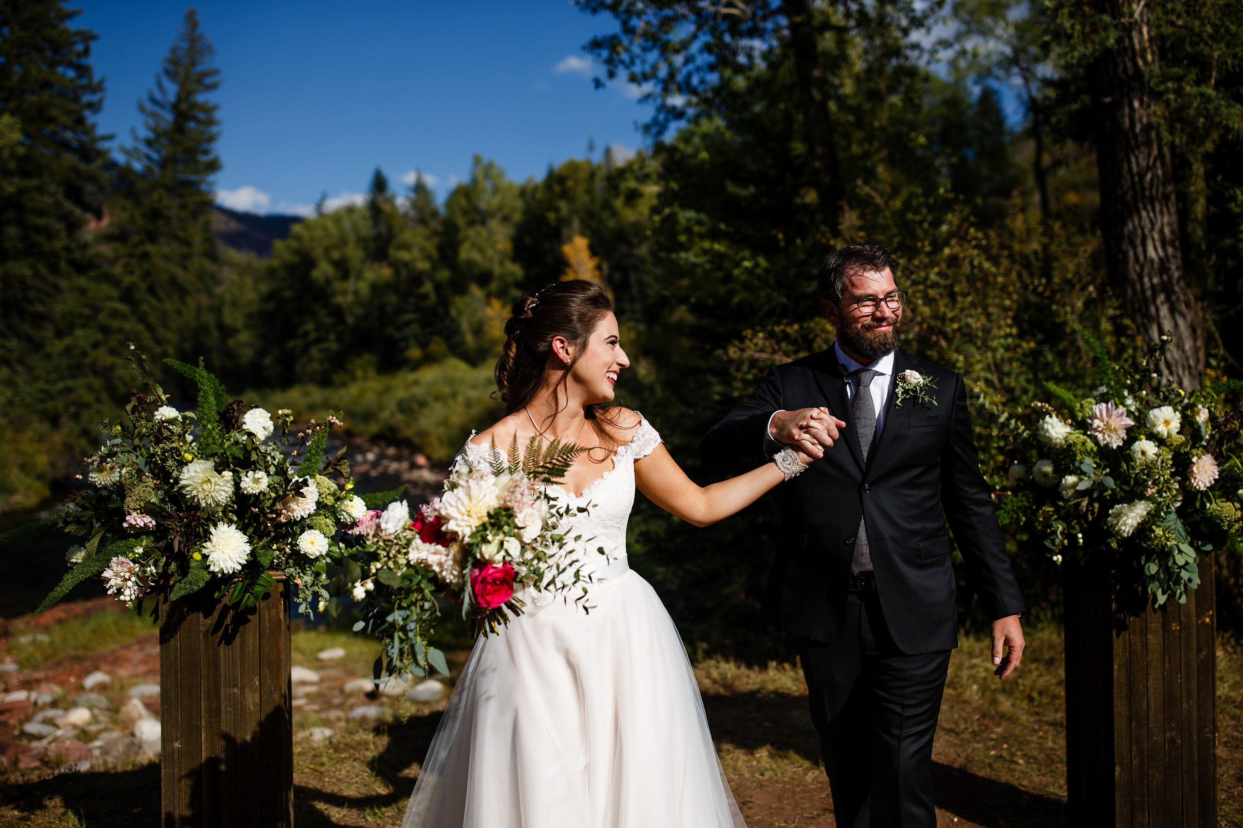 Mallory and Daniel celebrate as husband and wife after their fall Snowmass Cottages wedding