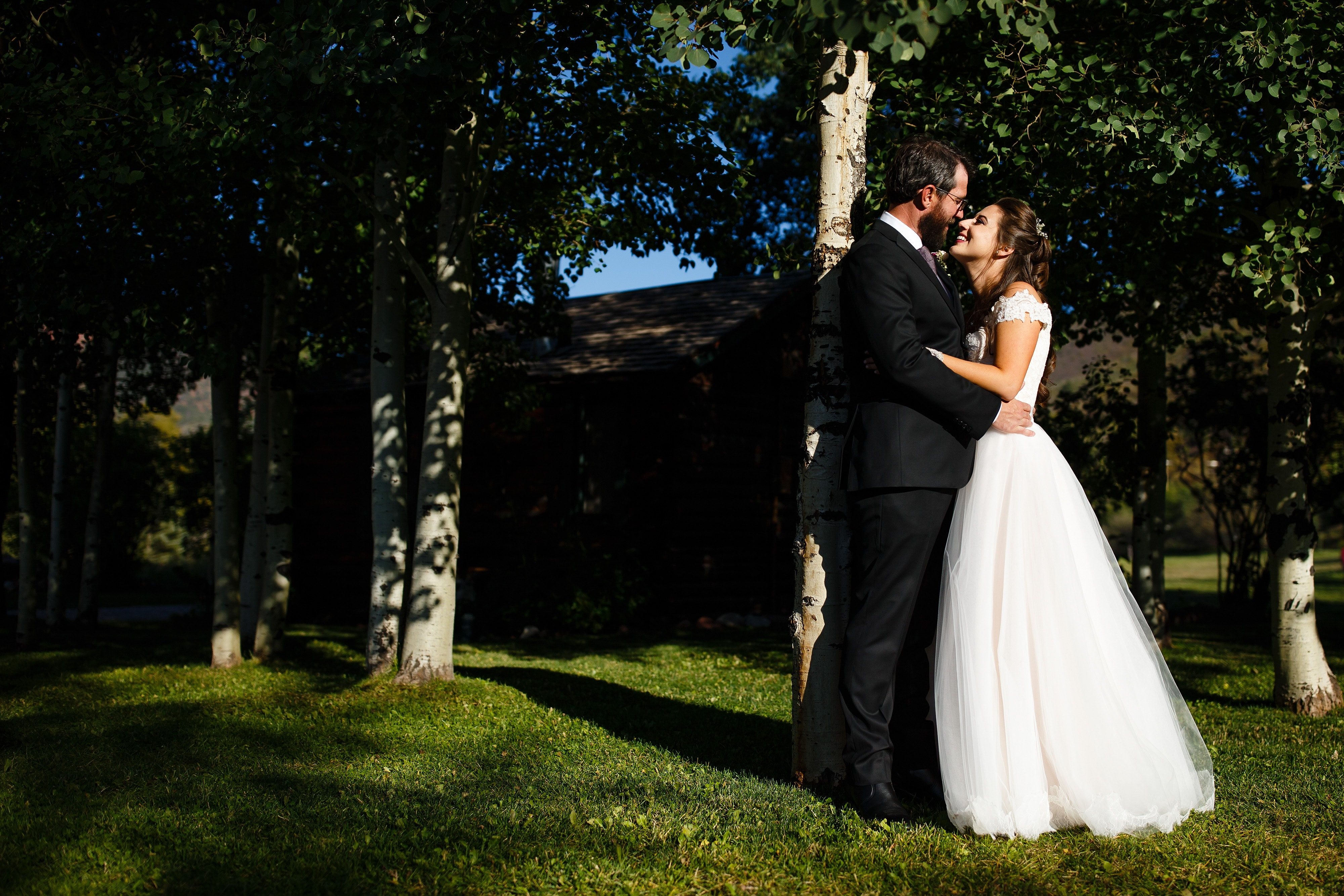 The couple enjoy a moment alone under the grove of aspen trees during their Snowmass Cottages wedding