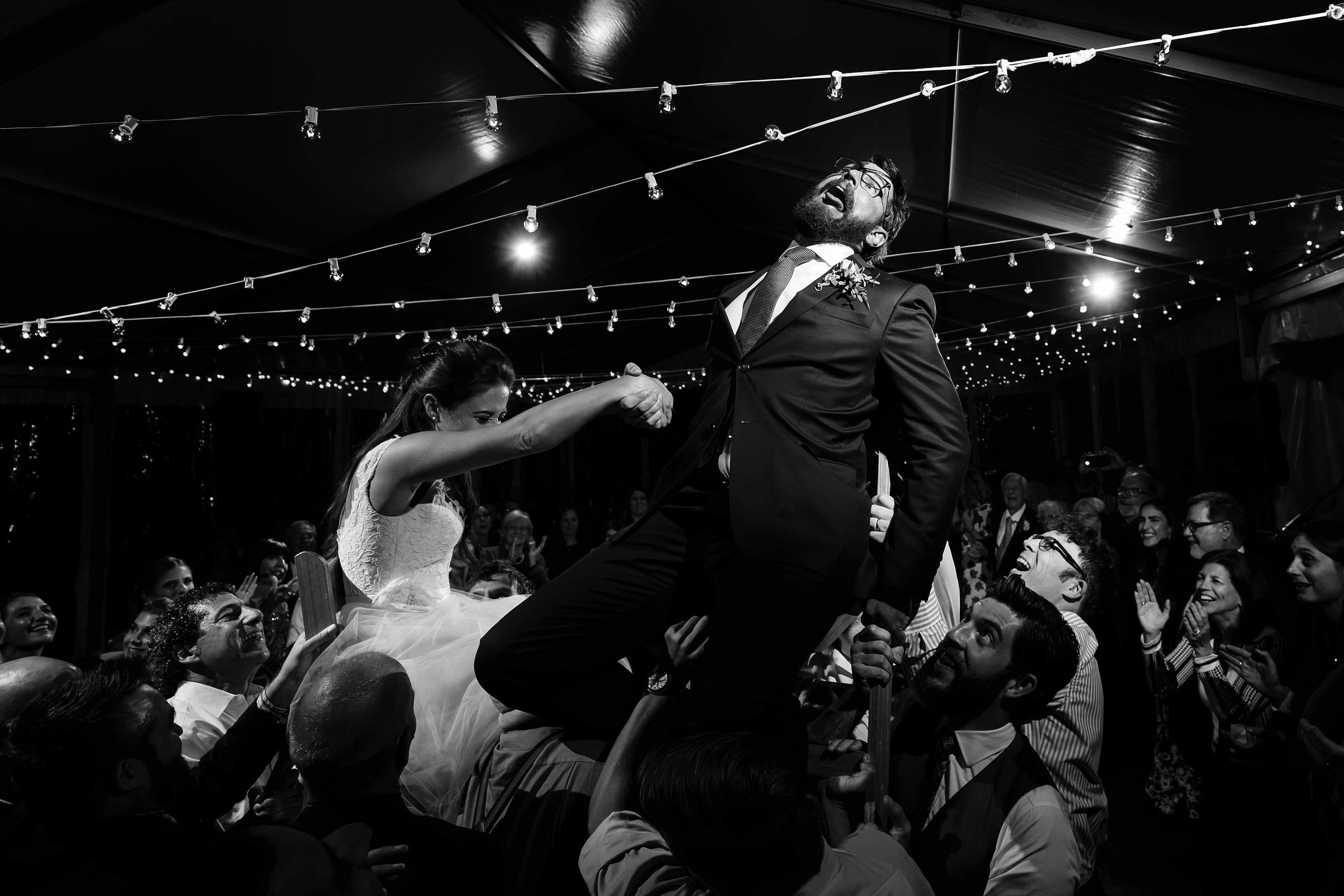Daniel and Mallory are hoisted on chairs duringa dance at their Snowmass Cottages wedding reception