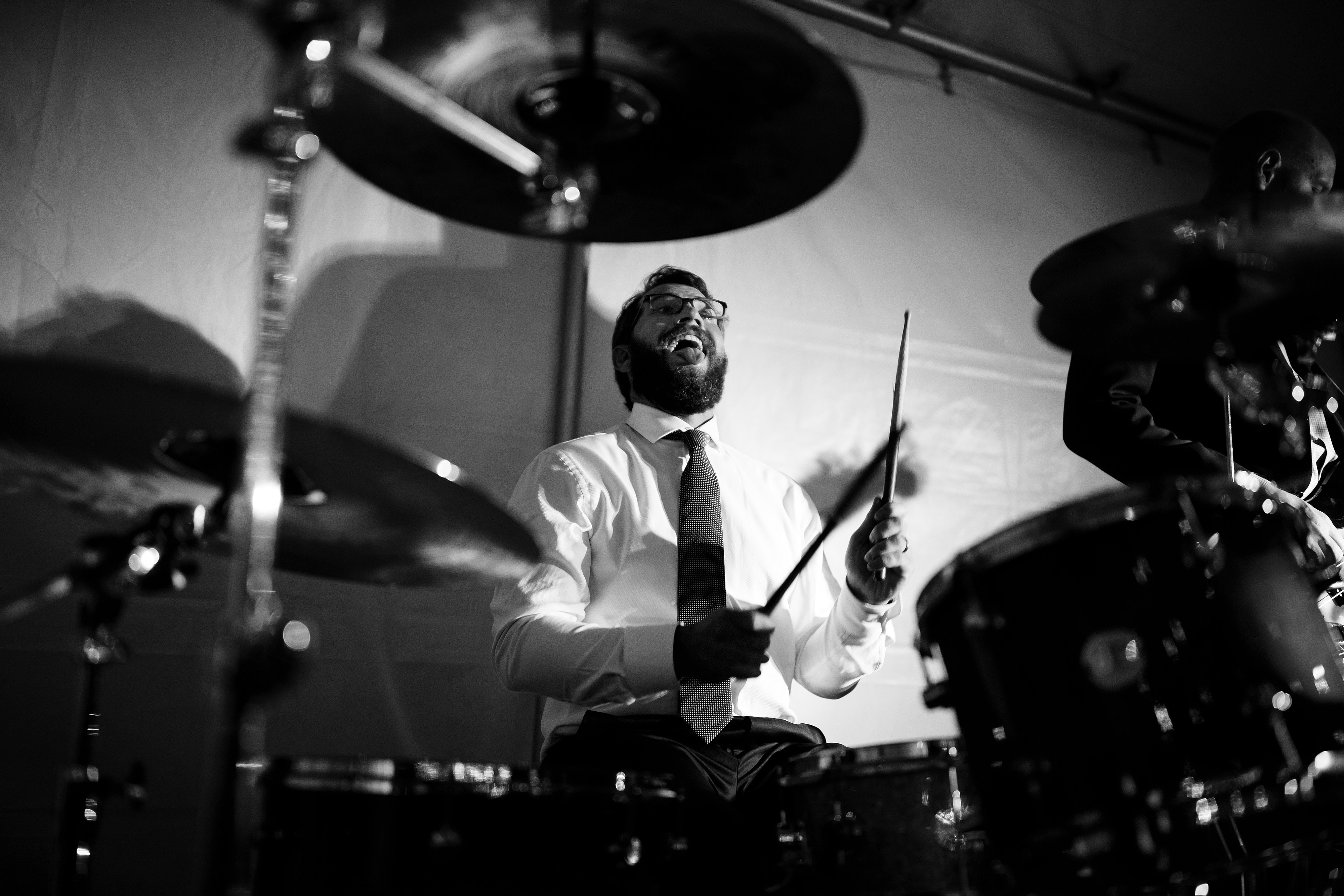 The groom plays the drums with his band during their wedding reception at Snowmass Cottages