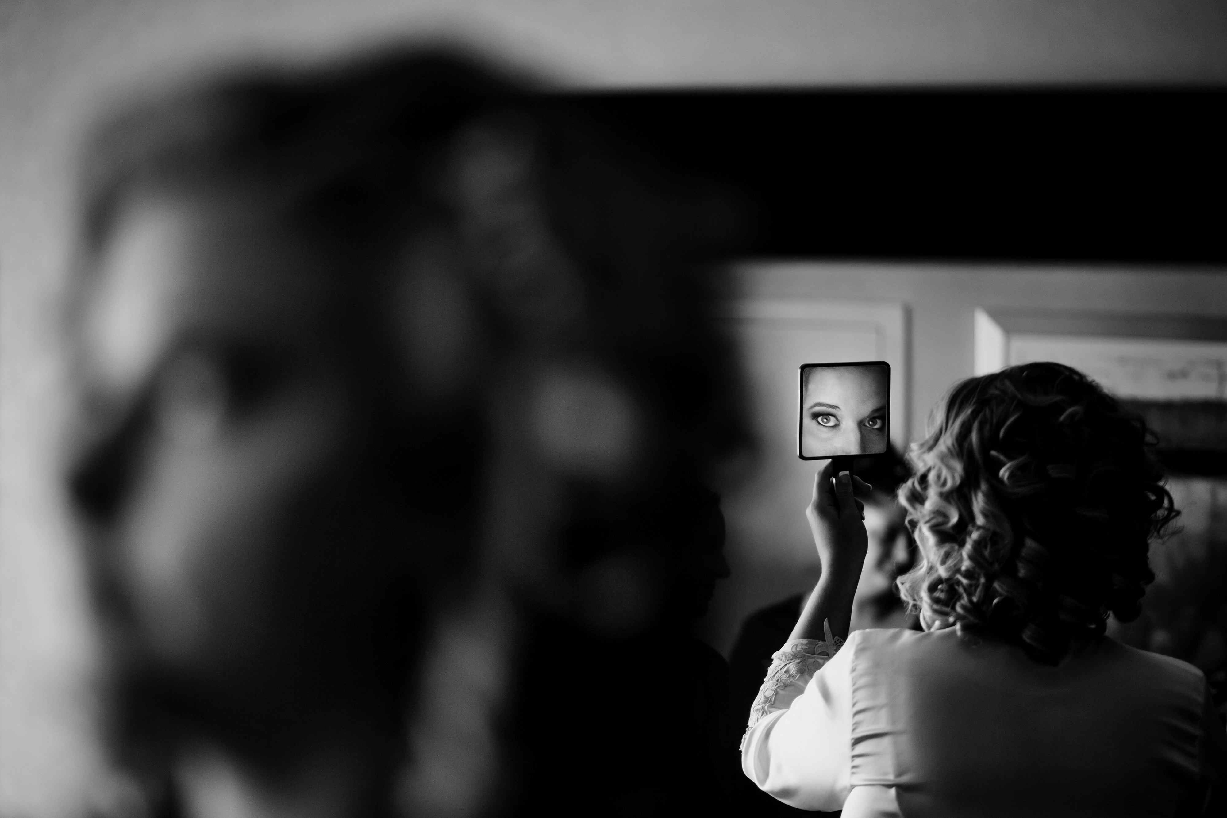 The bride is reflected in a mirror while getting ready at the Westin in Denver
