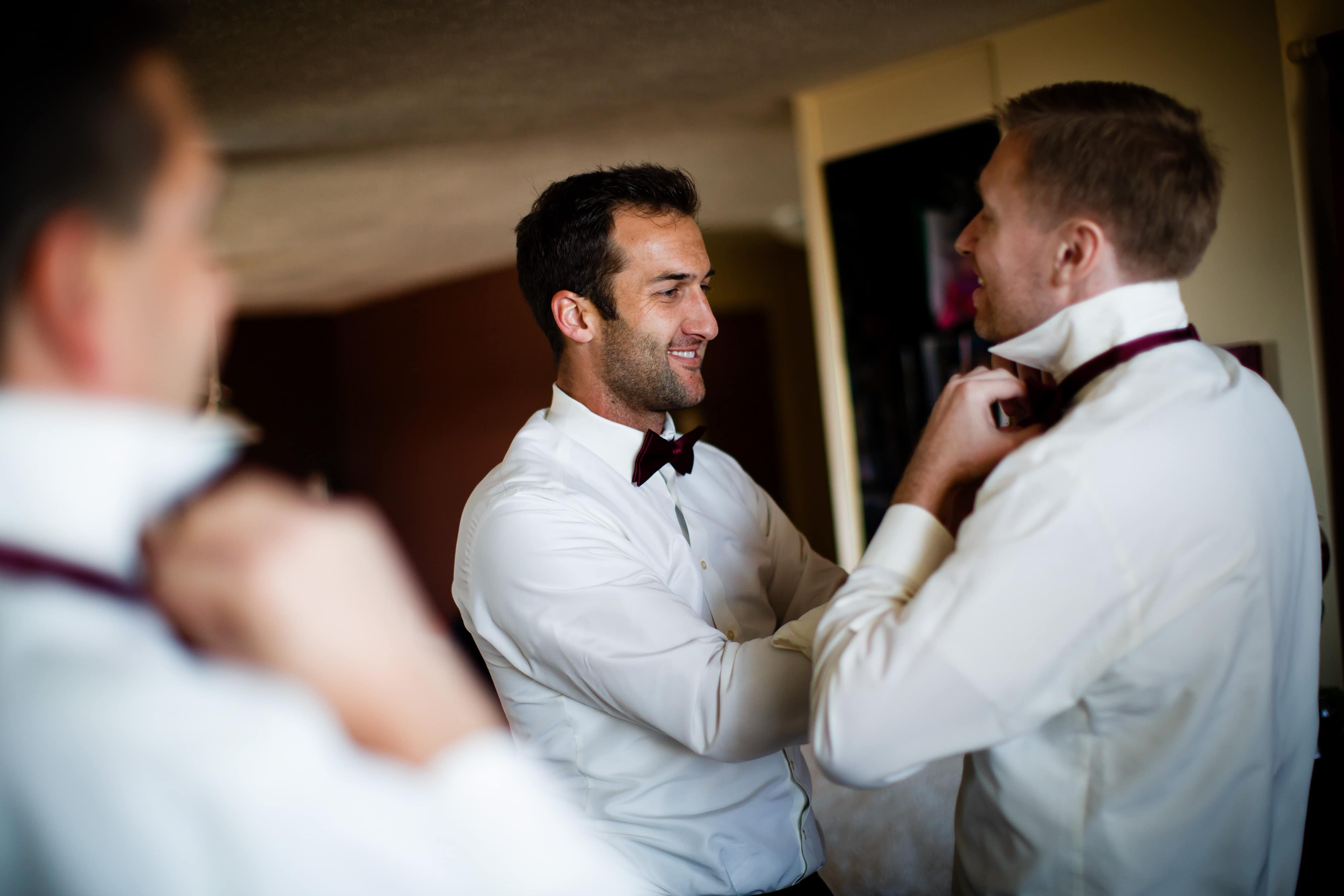 A groomsman helps Ryan with his tie