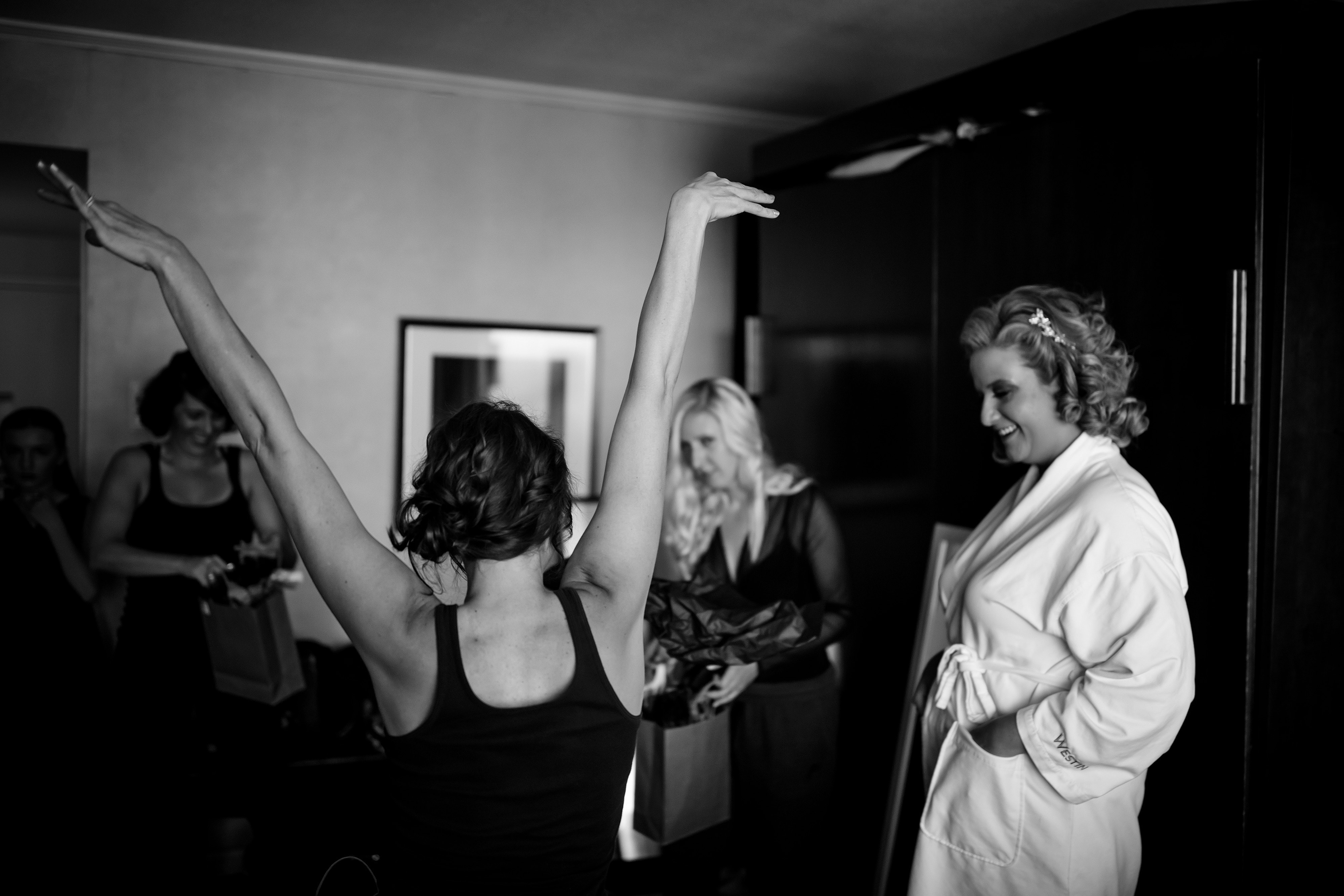 A bridesmaid celebrates while getting ready at the Westin