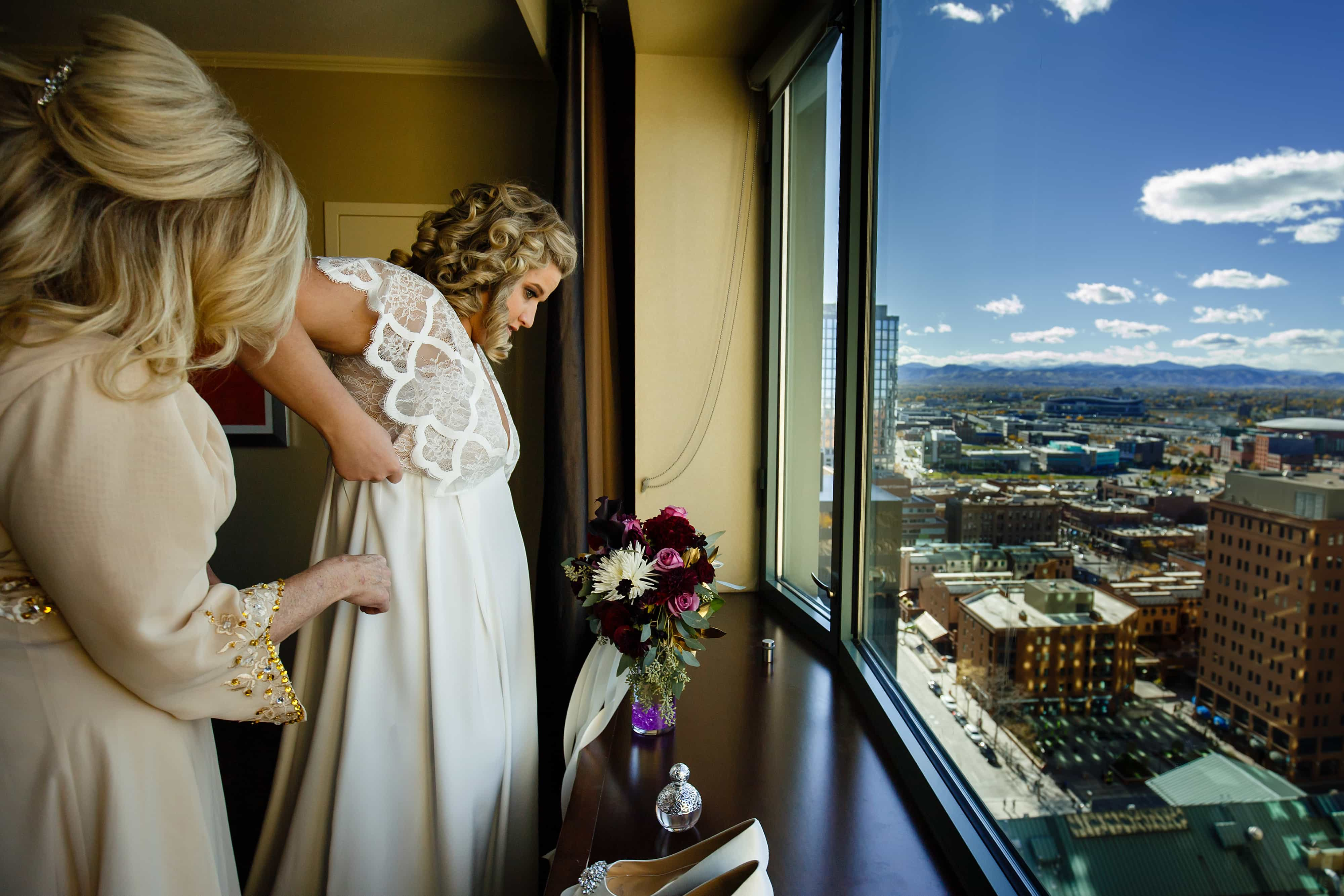 Sarah gets some help from her mother while putting on her wedding dress with a view of downtown Denver and the mountains at the Westin in Denver