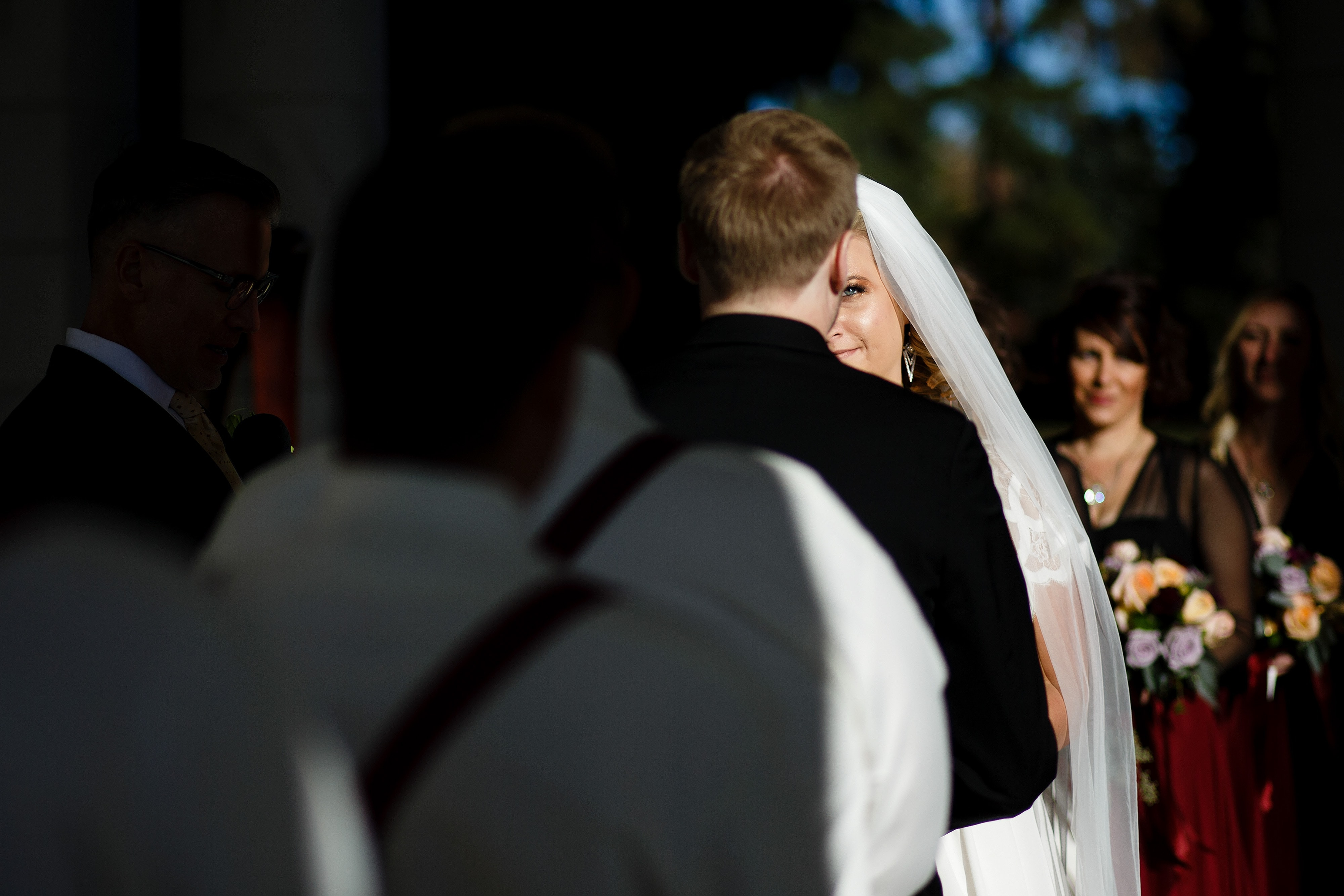 A sliver of light illuminates the bride during the wedding at Cheesman Park in Denver