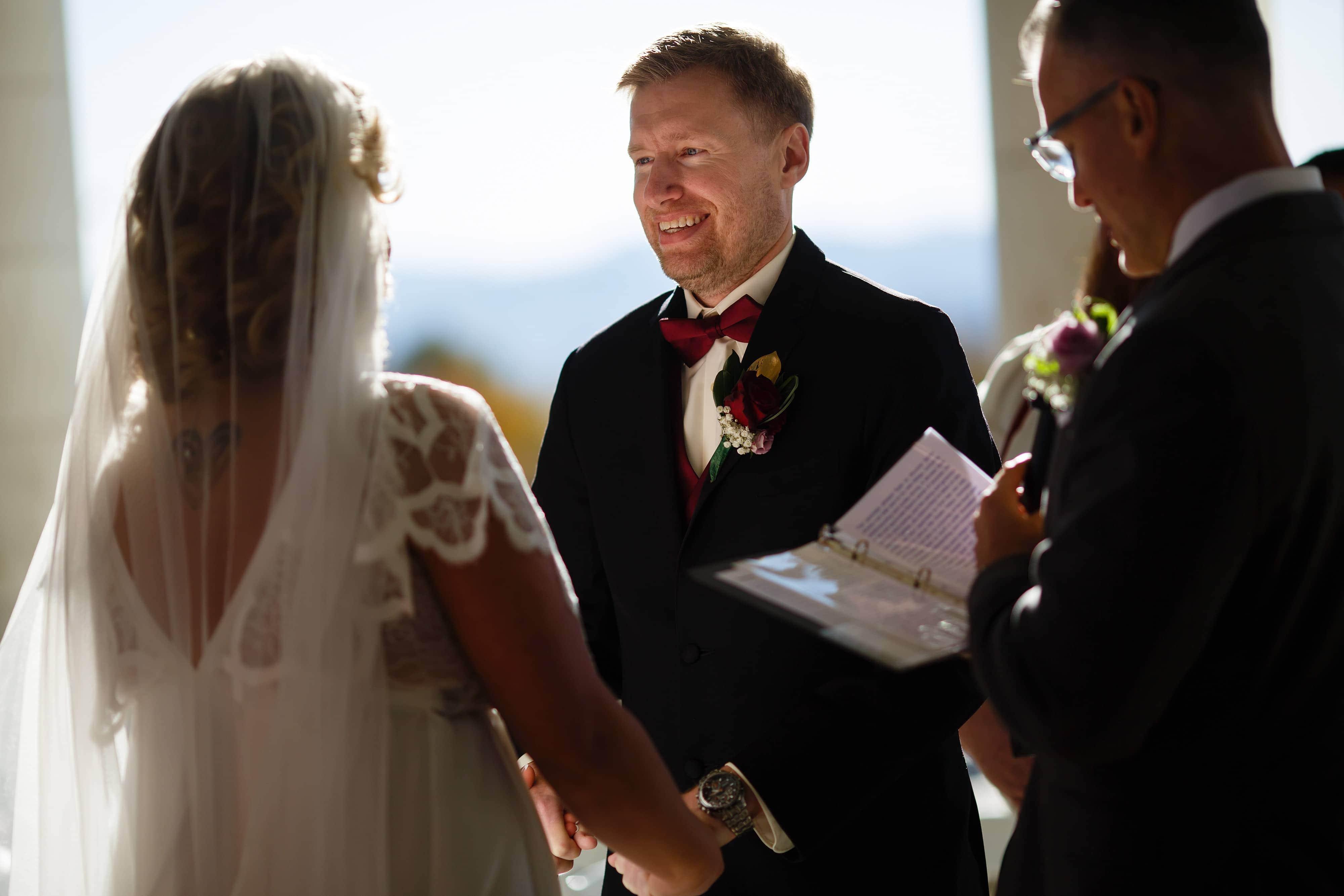 Ryan smiles at Sarah during their wedding ceremony at Cheesman Park